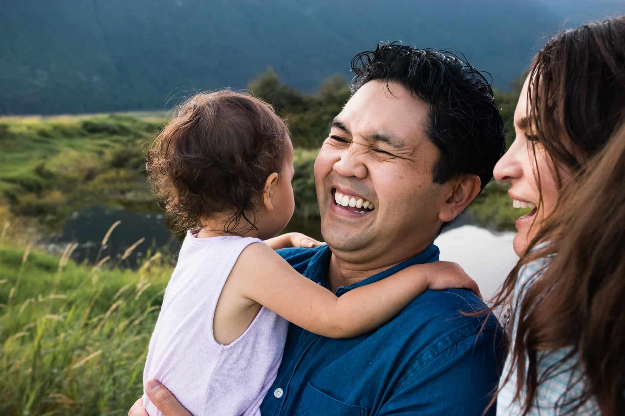 mom and dad laughing and hugging toddler girl