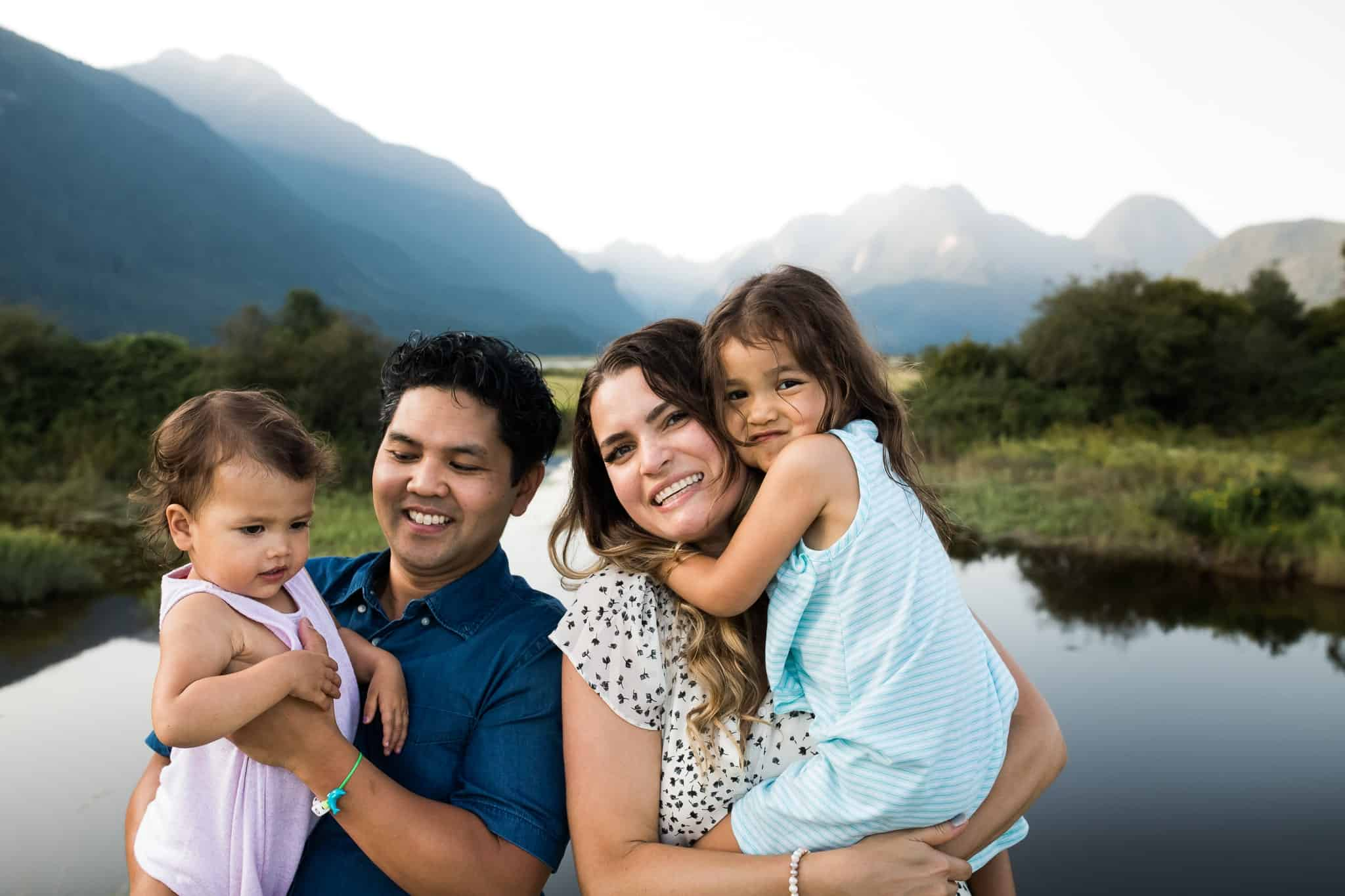 family holding little girls with lake and mountains in the background
