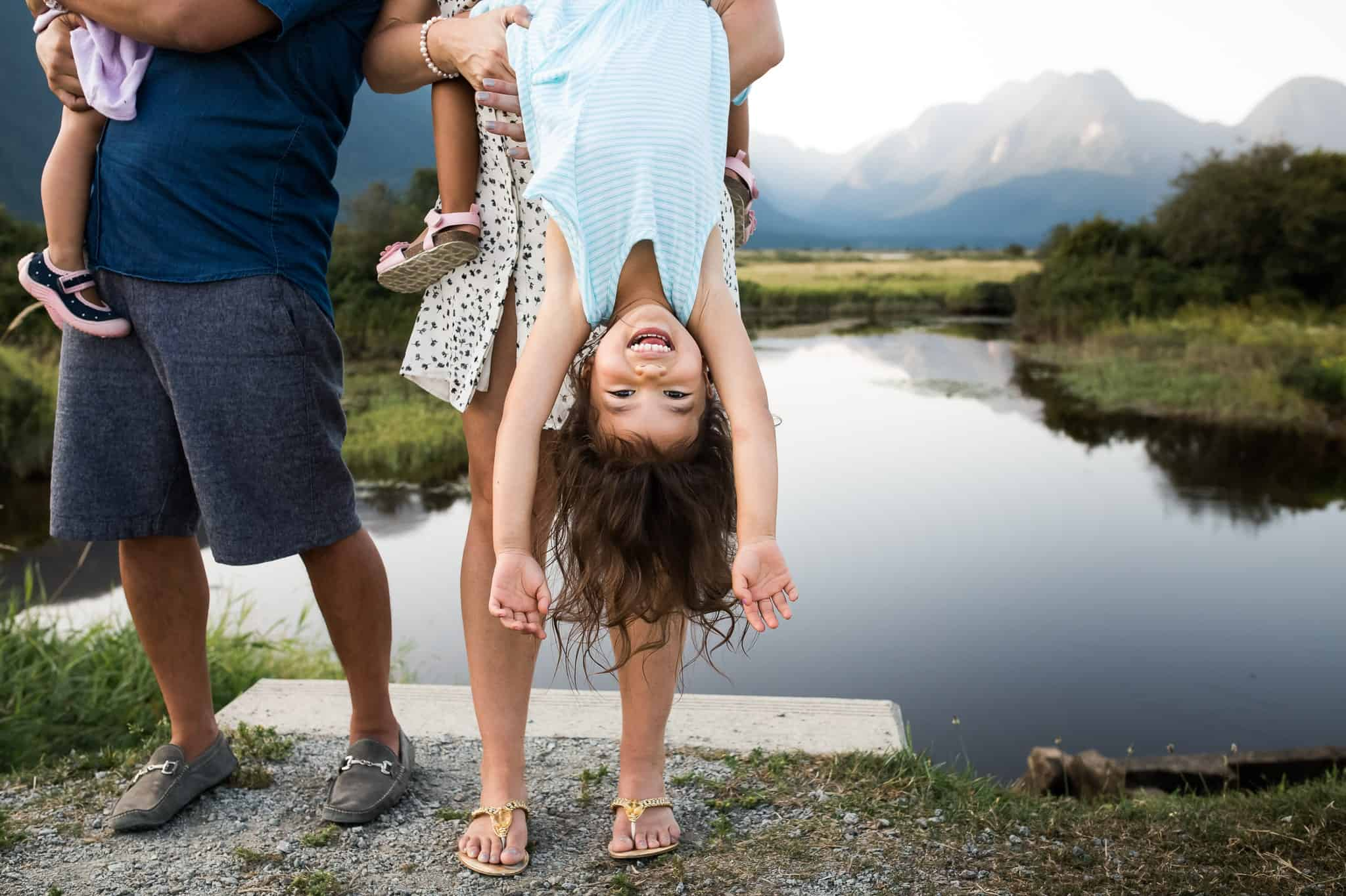 family holding kids with little girl swinging upside down with lake and mountains behind