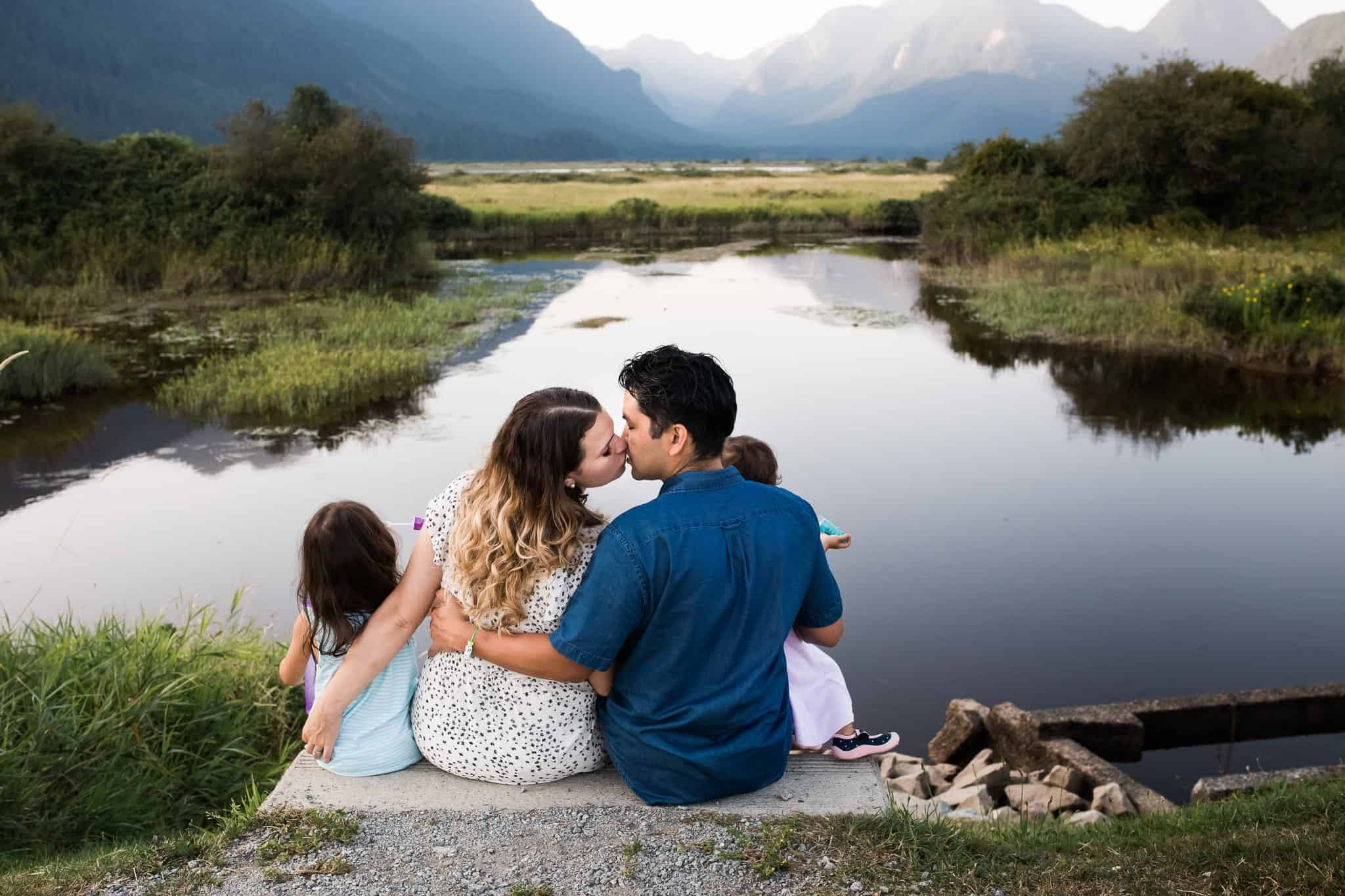 family sitting by lake and mountains, with mom and dad kissing and holding little girls