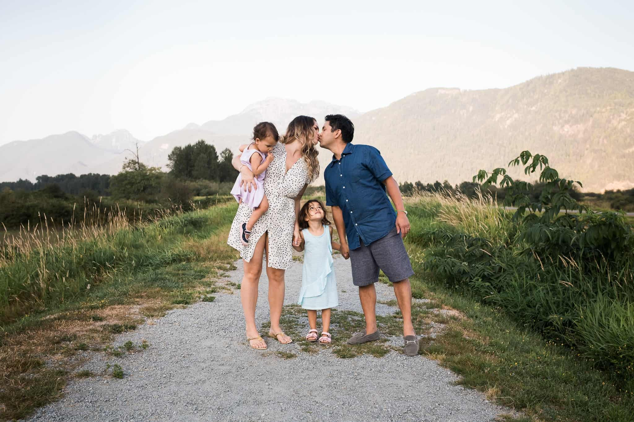 family with two little girls holding hands and mom and dad kissing