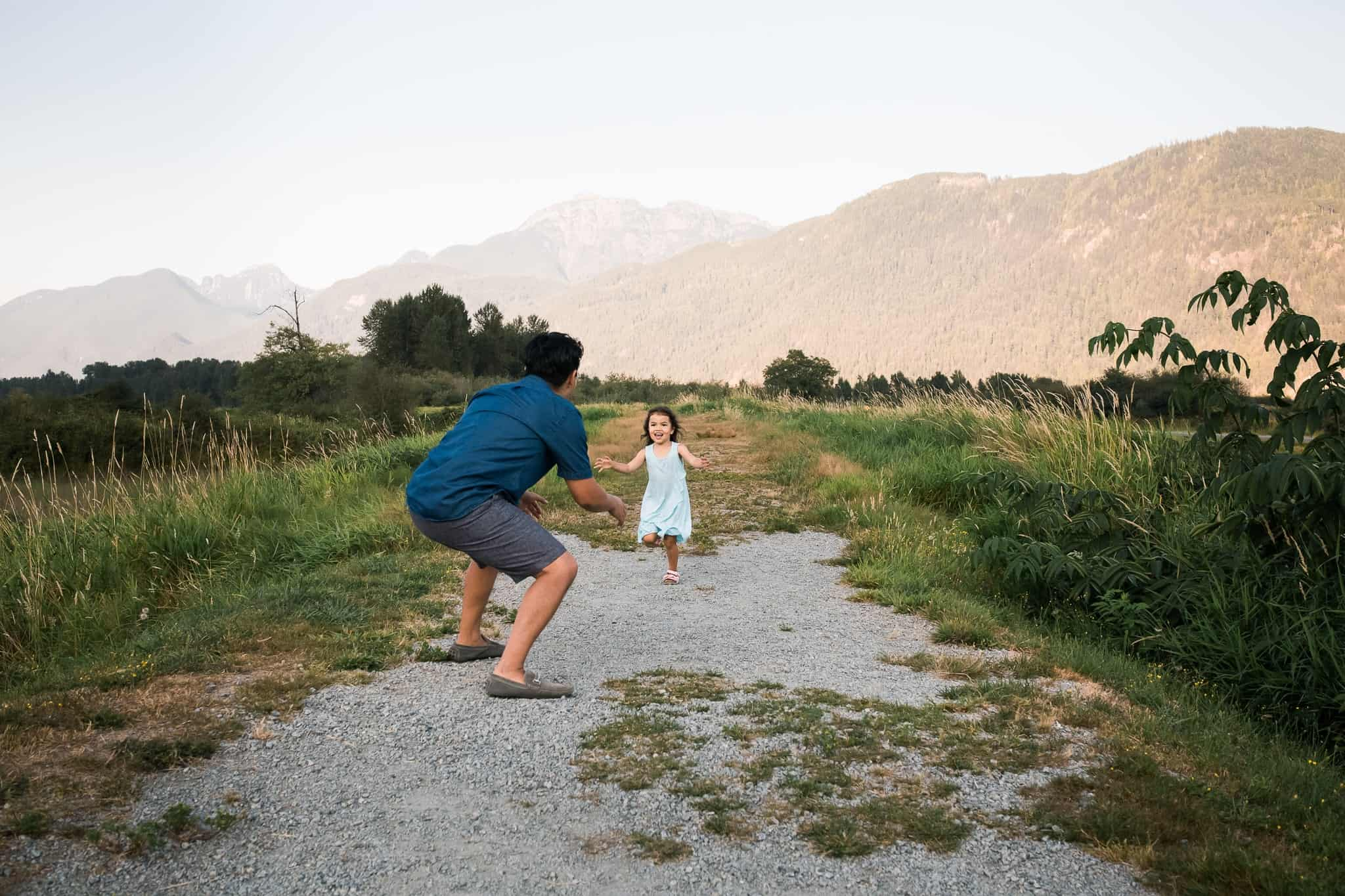 little girl running into her daddy's arms with mountains in the background