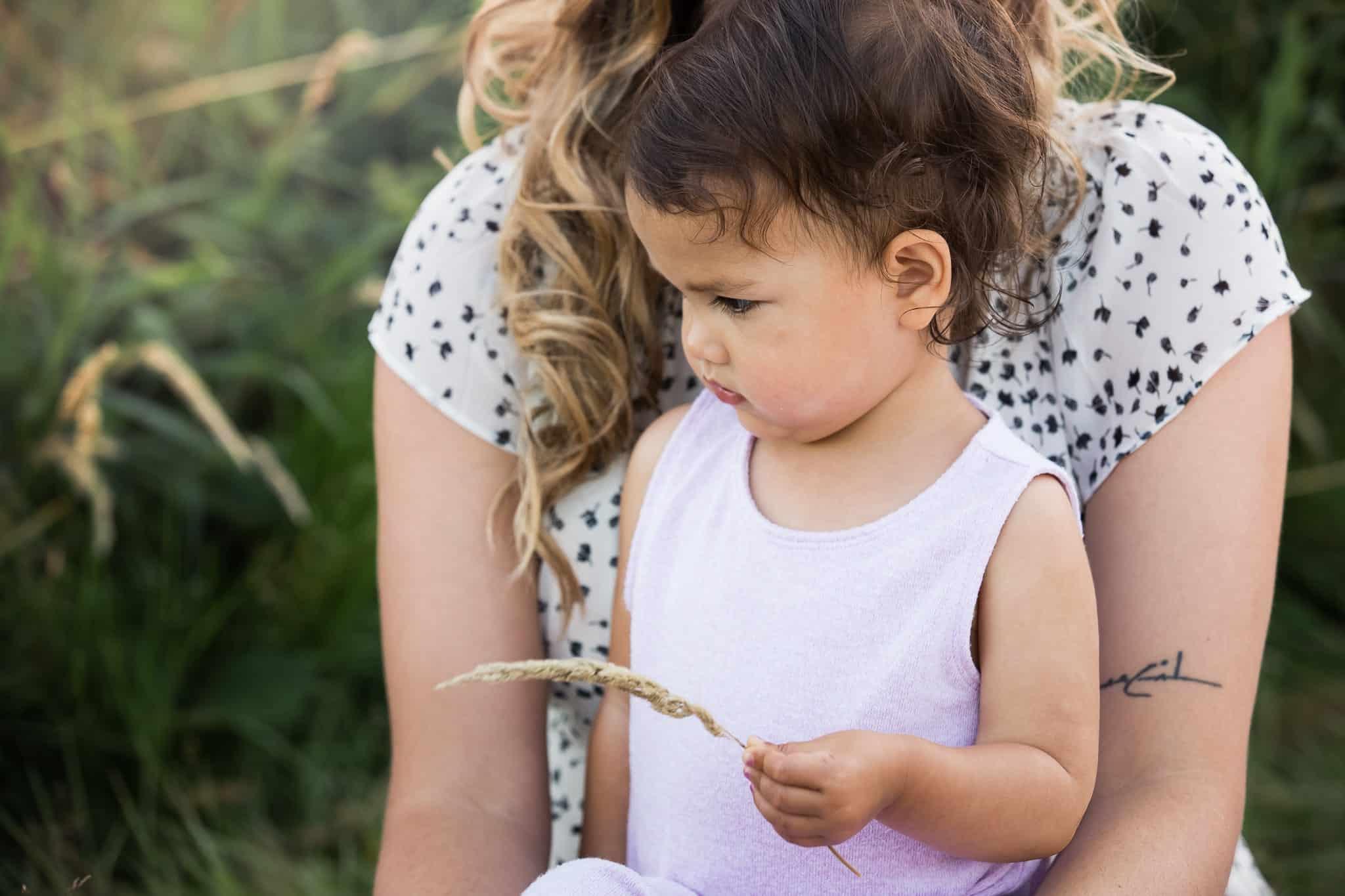 mom holding little girl picking grass in her lap