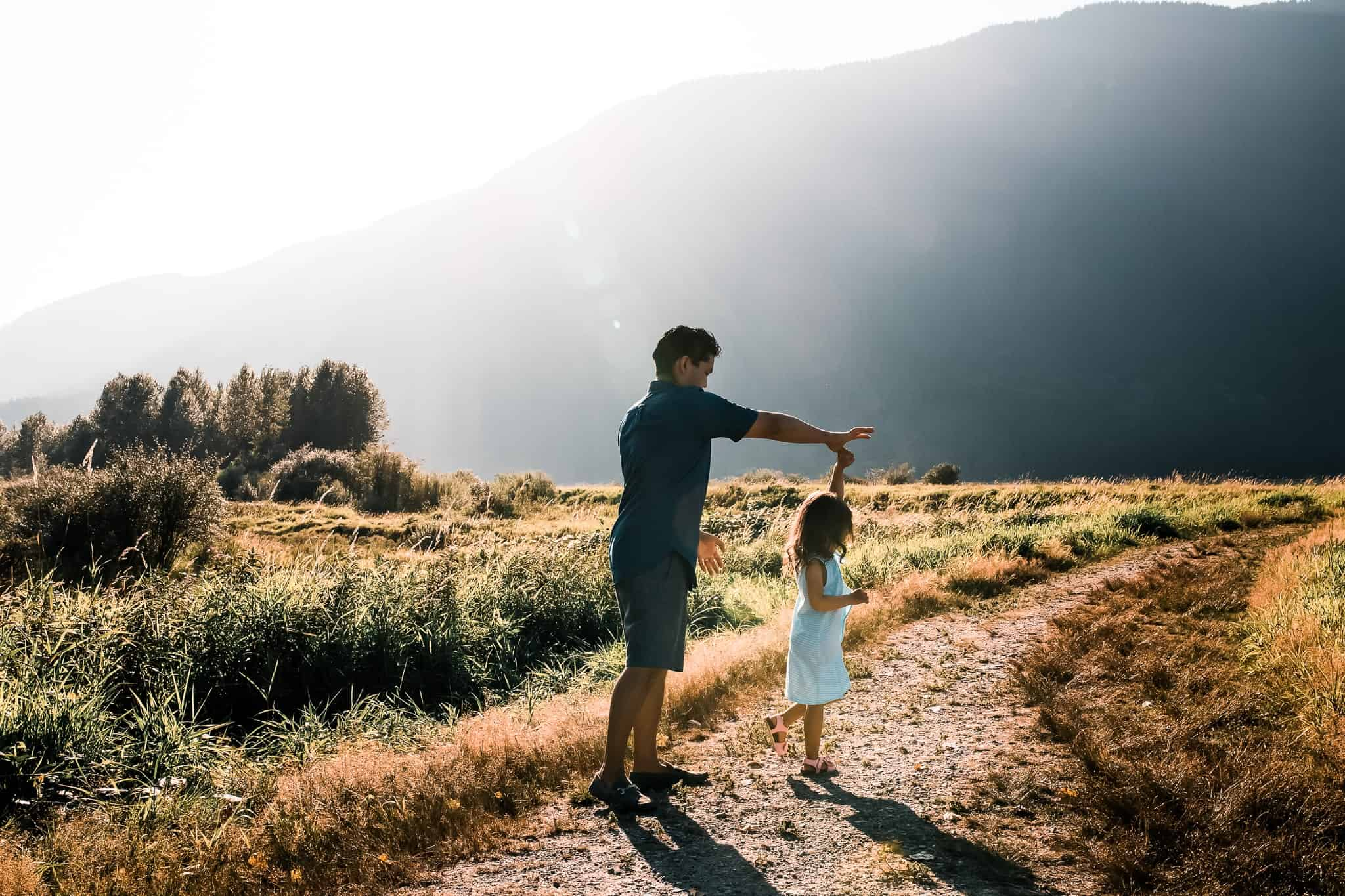dad dancing with little girl in a field with mountains behind