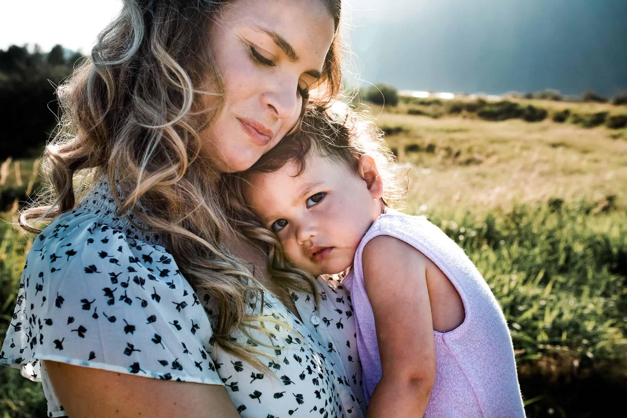 mom holding little girl against her shoulder in the sunset