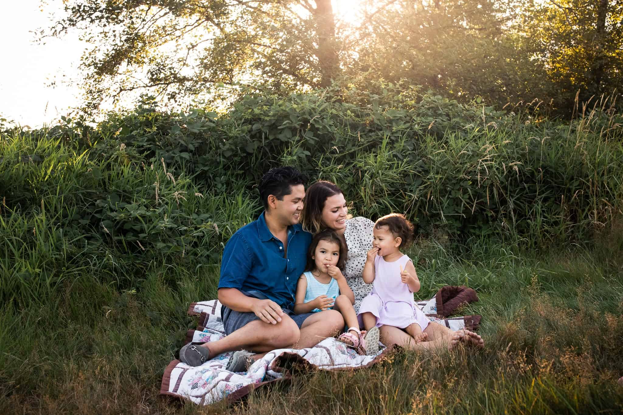 family sitting on blanket in sunset and field eating snacks and snuggling