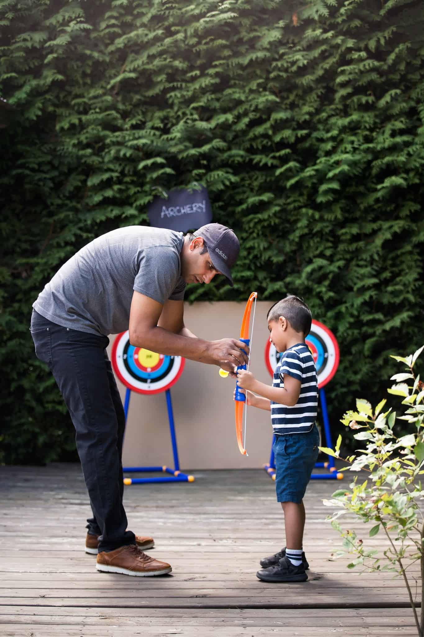 dad teaching son archery