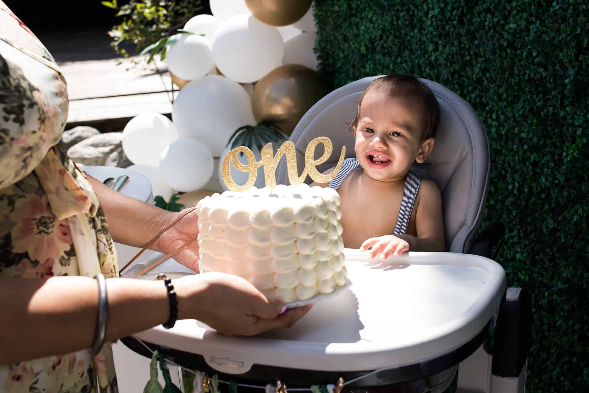 baby with cake celebrating first birthday