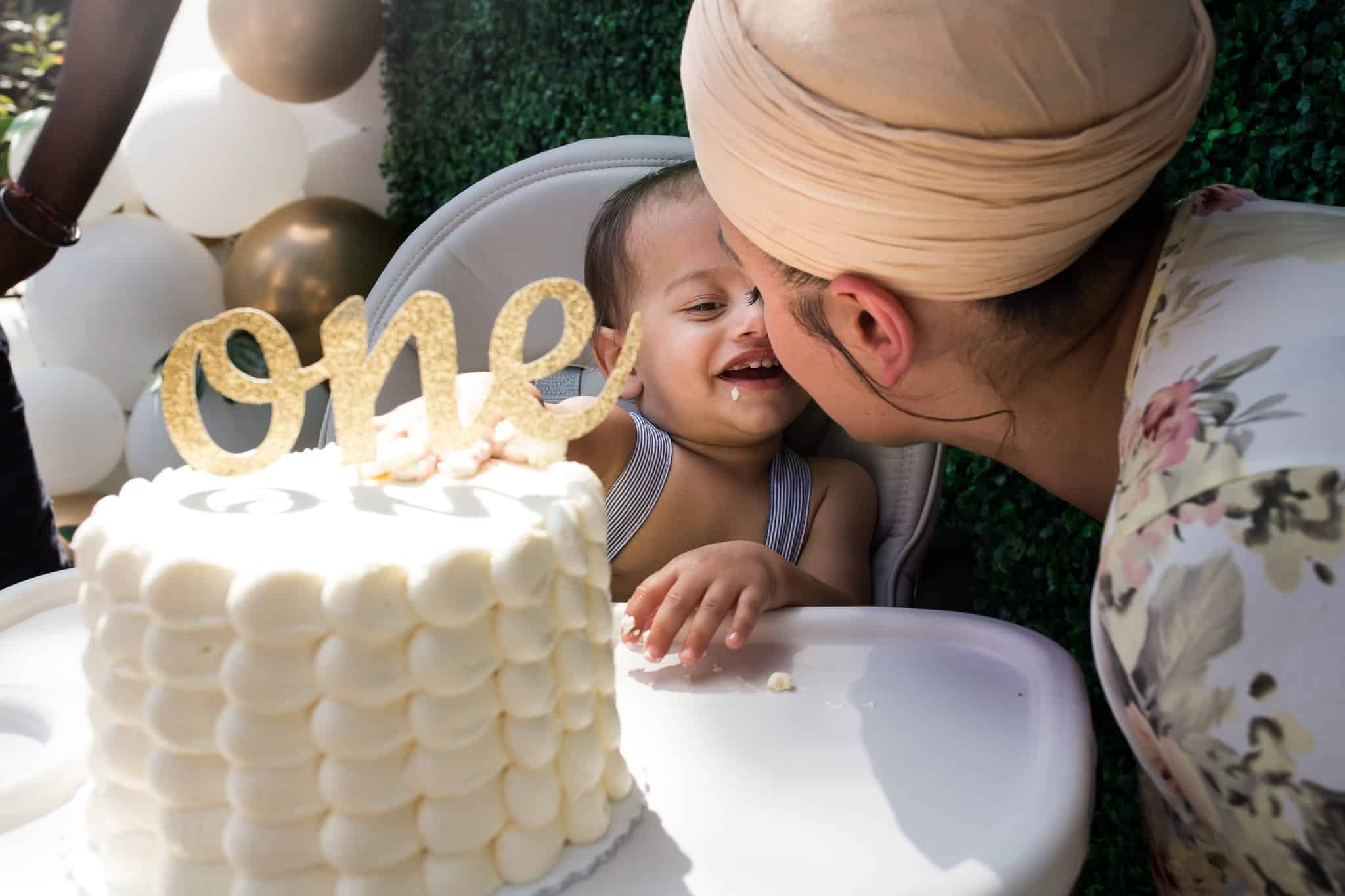 baby with cake kissing his mom
