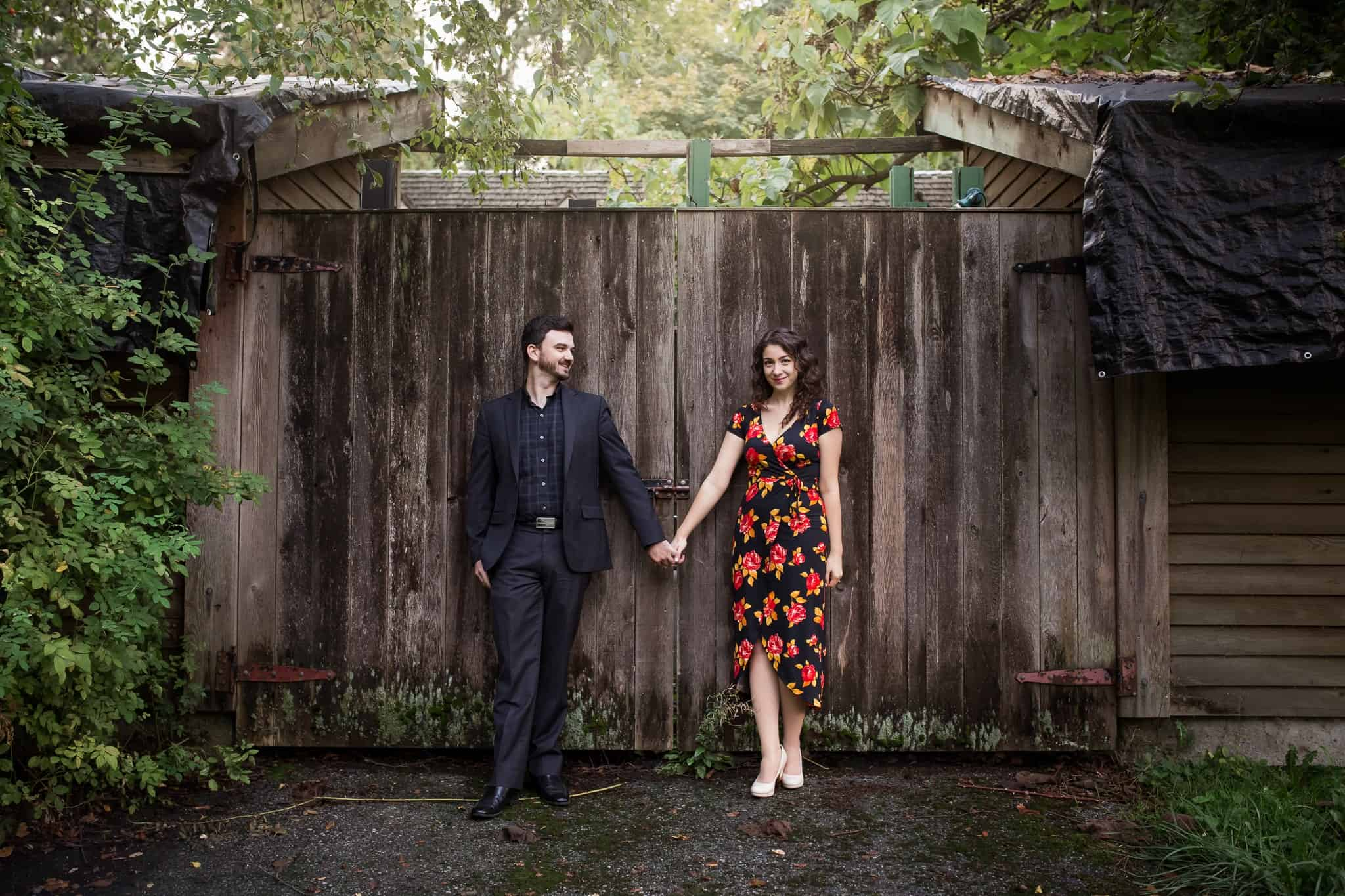 couple holding hands against a wood wall and looking at the camera