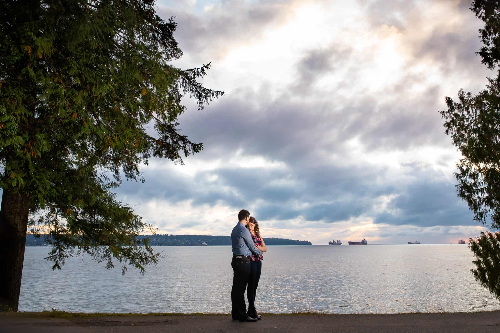 man holding a woman and kissing her head with ocean and sunset in the background