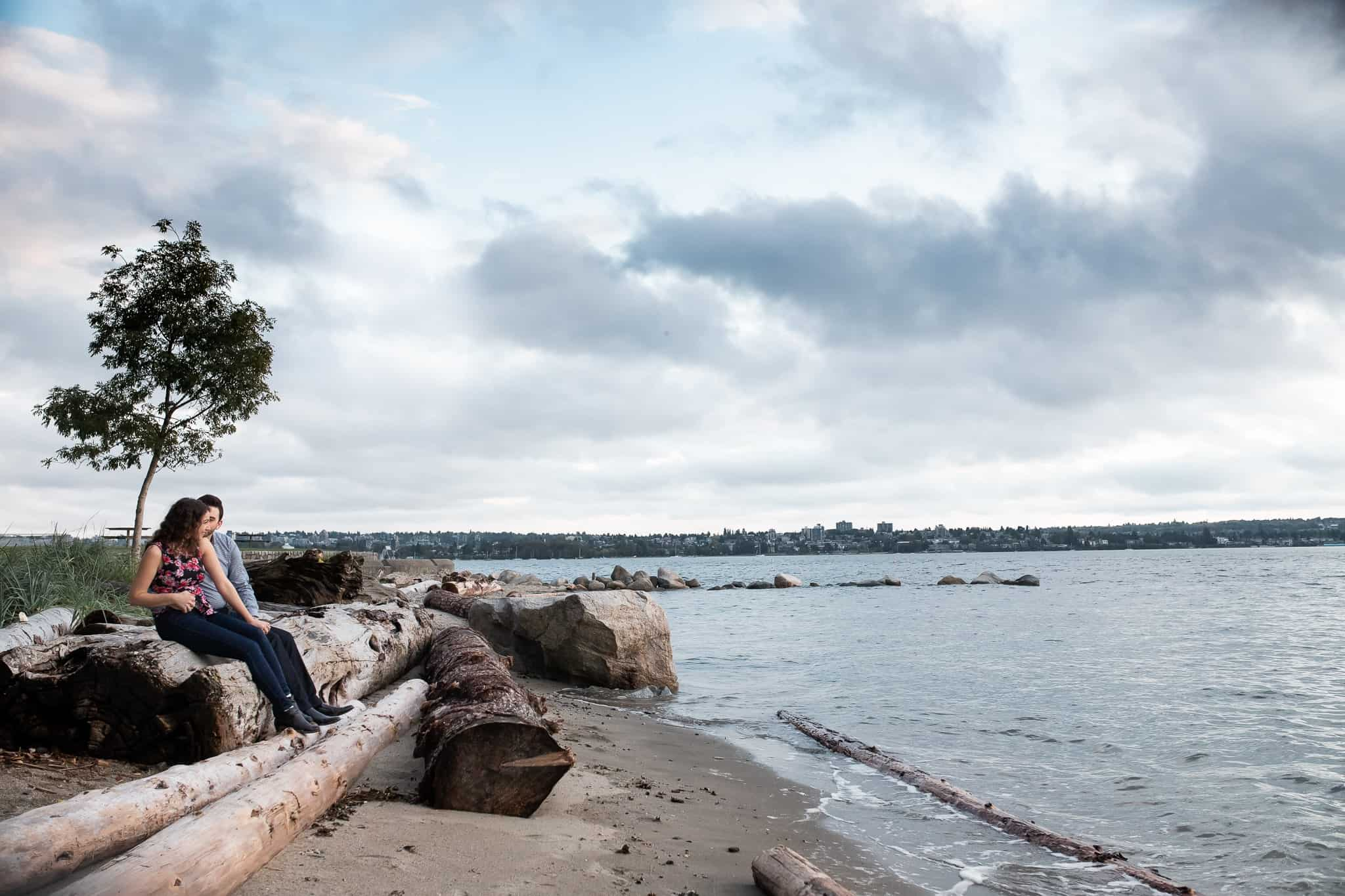 couple sitting on logs on the beach by the ocean with city scape in background