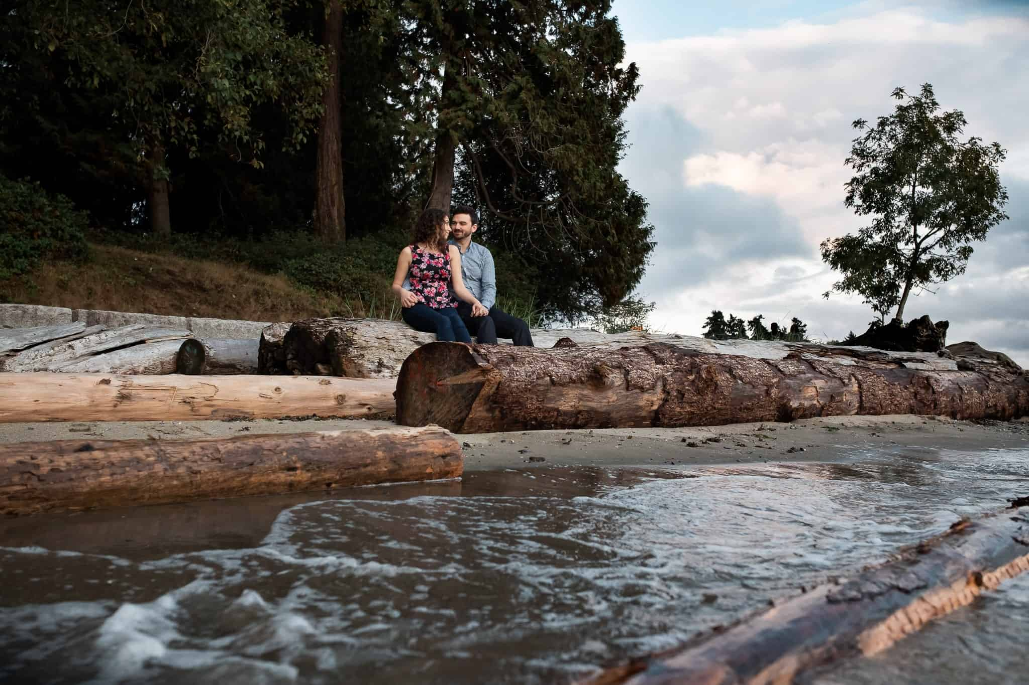 couple sitting on drift wood logs holding hands on the beach