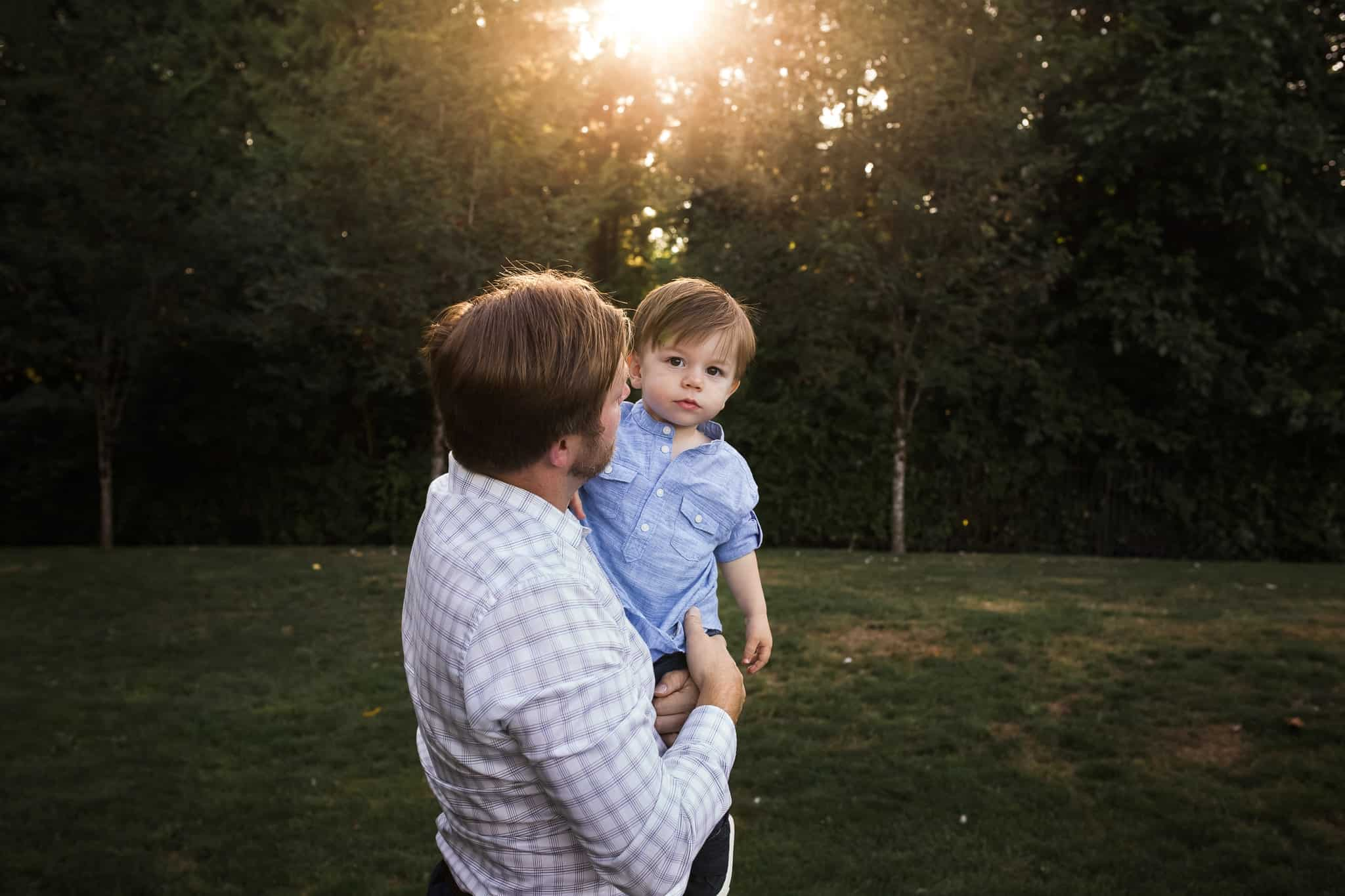 dad holding his toddler son in the sunset