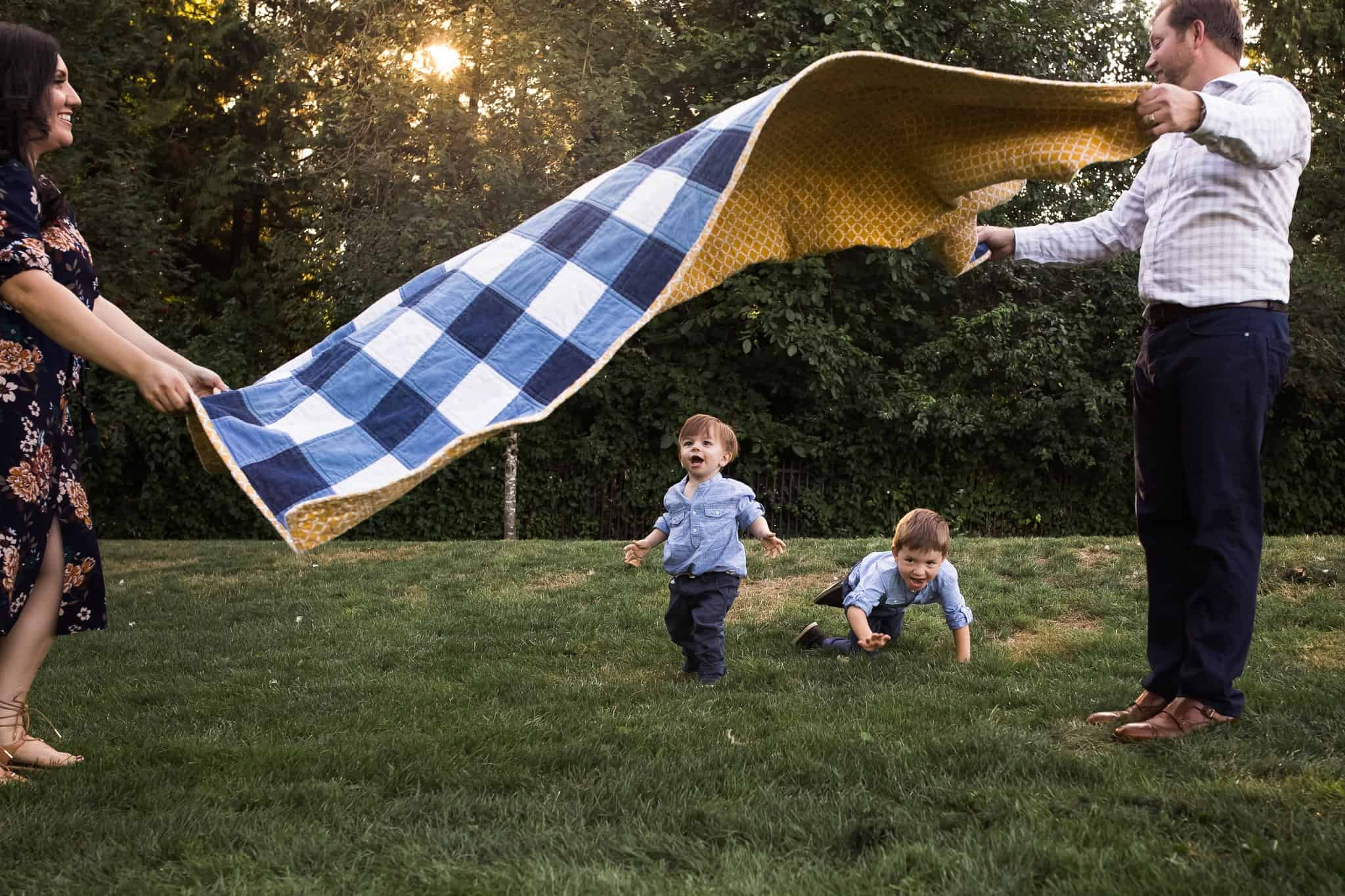 two little boys running under a blanket that mom and dad are holding up for them