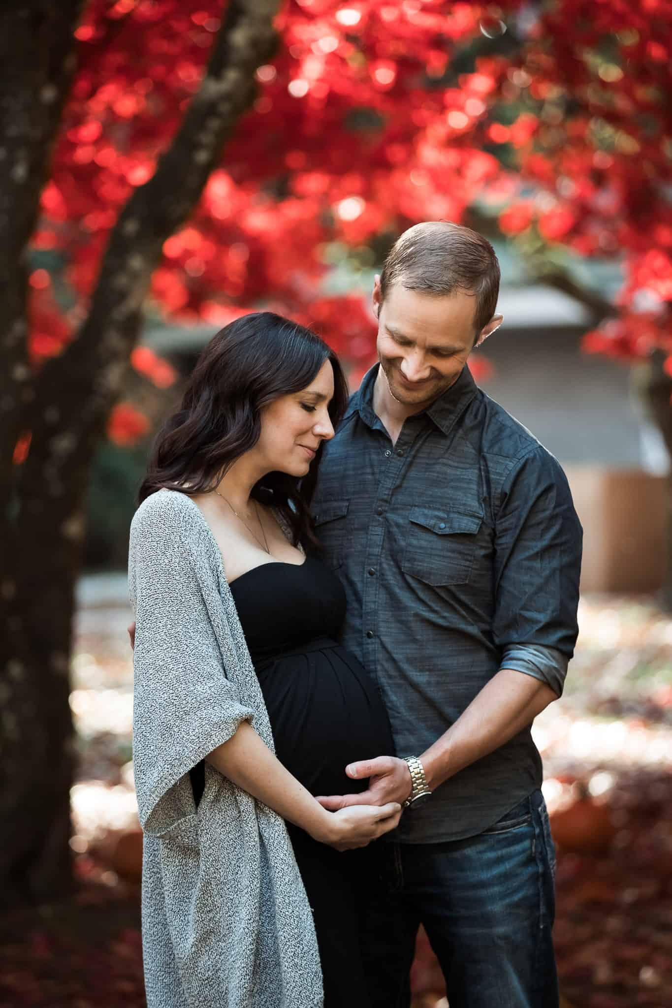 couple holding pregnant belly under red leafed trees