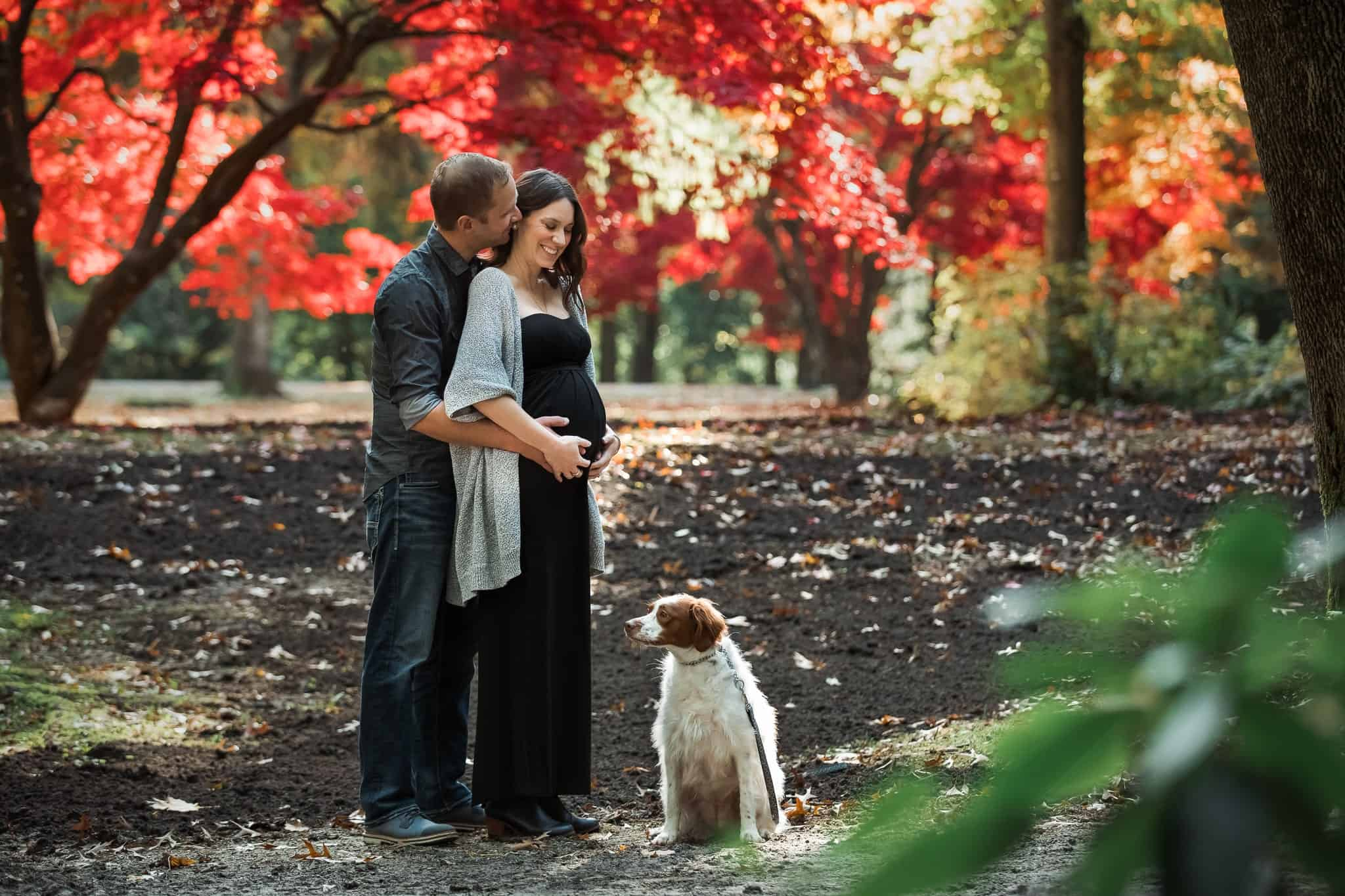 pregnant couple hugging with dog in autumn forest