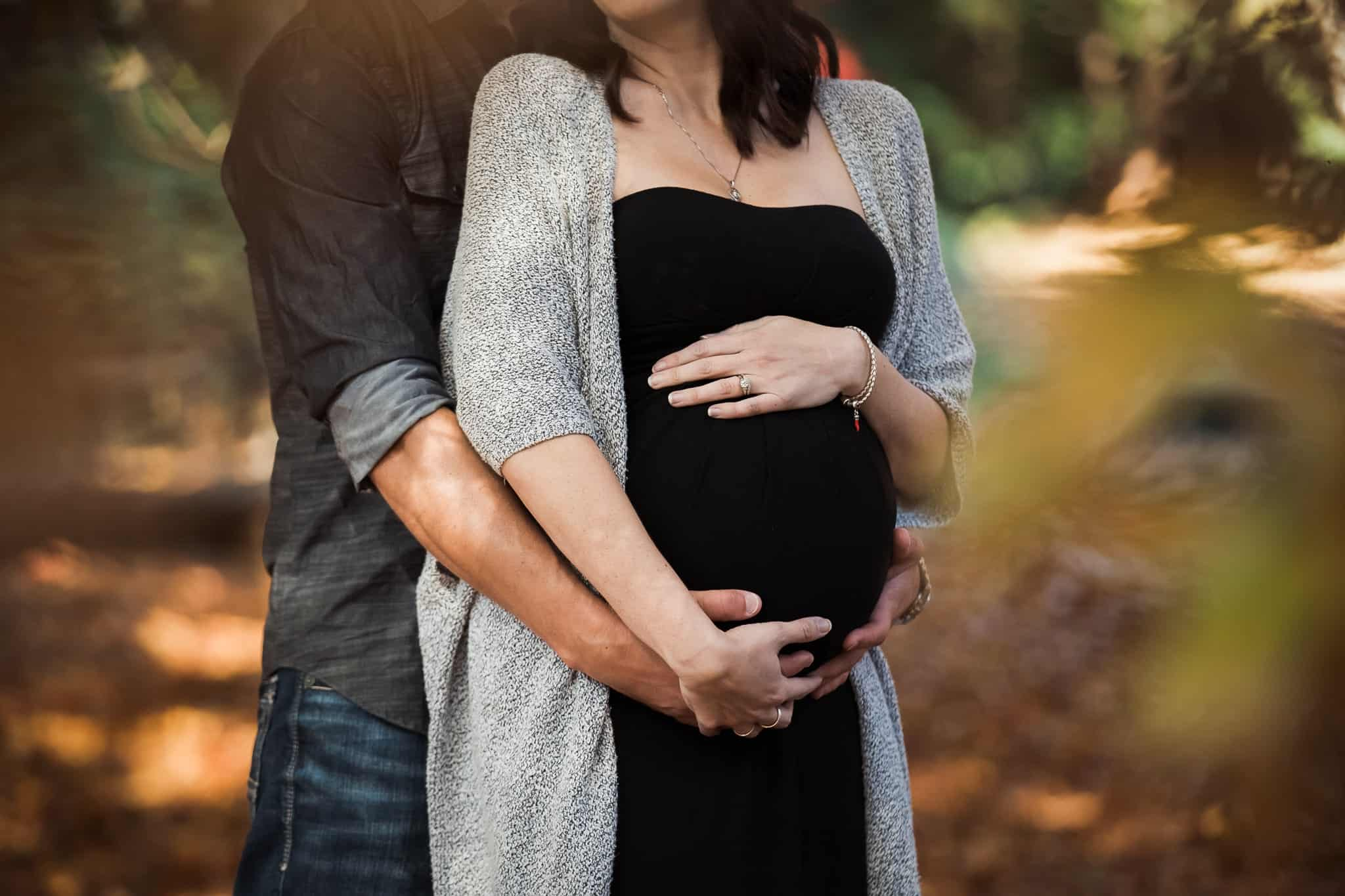 couple holding pregnant belly in autumn leaves