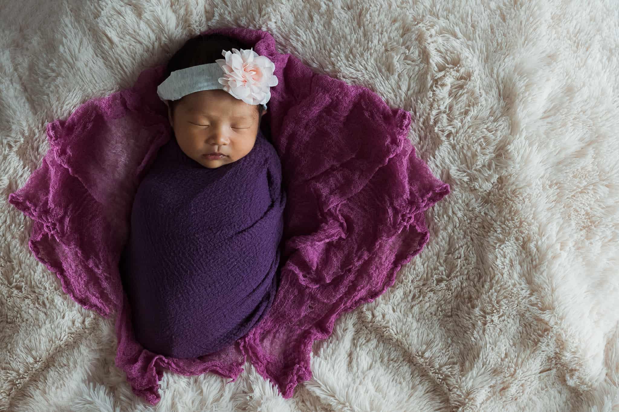 newborn baby swaddled in purple wrap