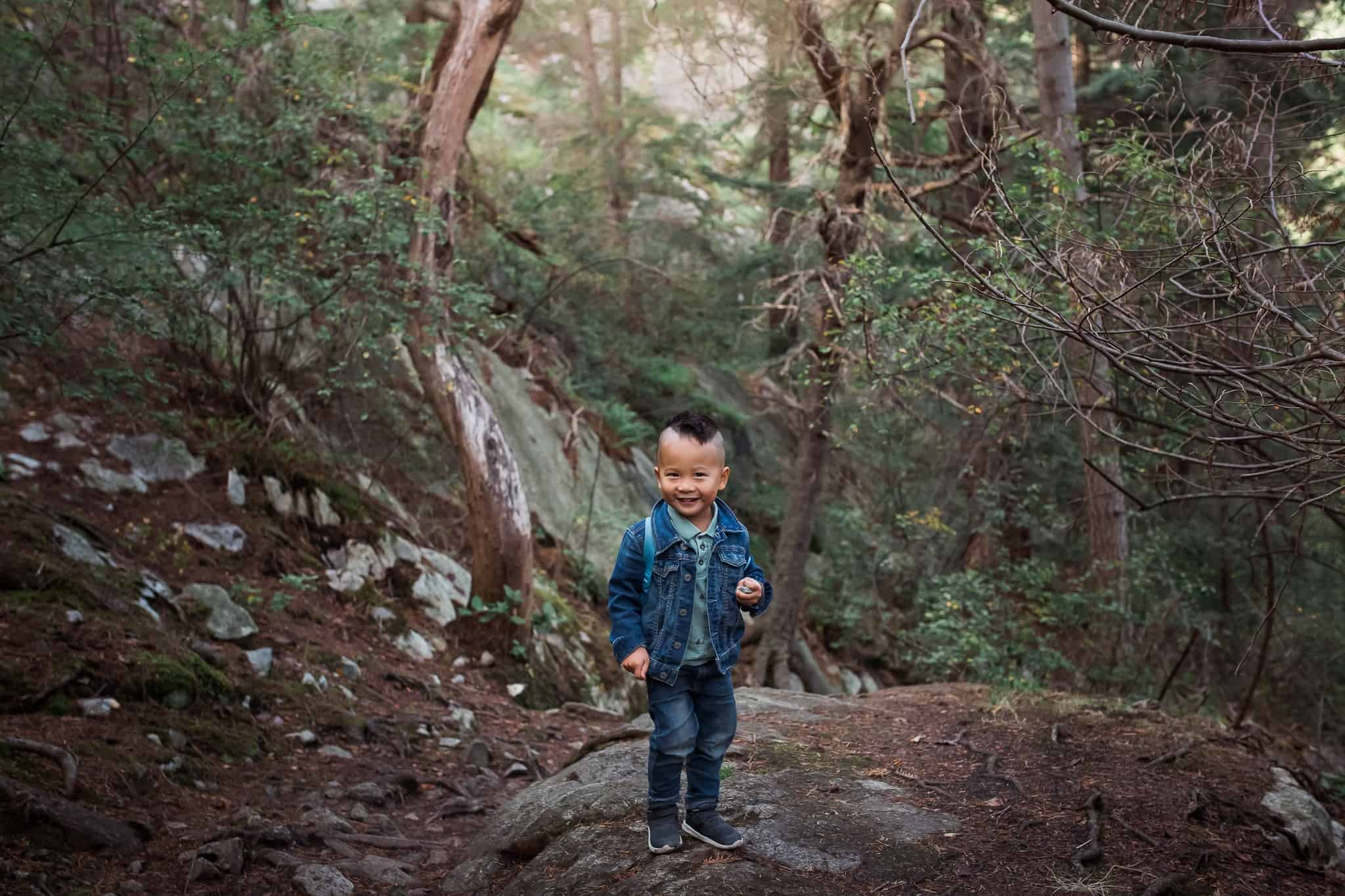 toddler boy exploring in forest