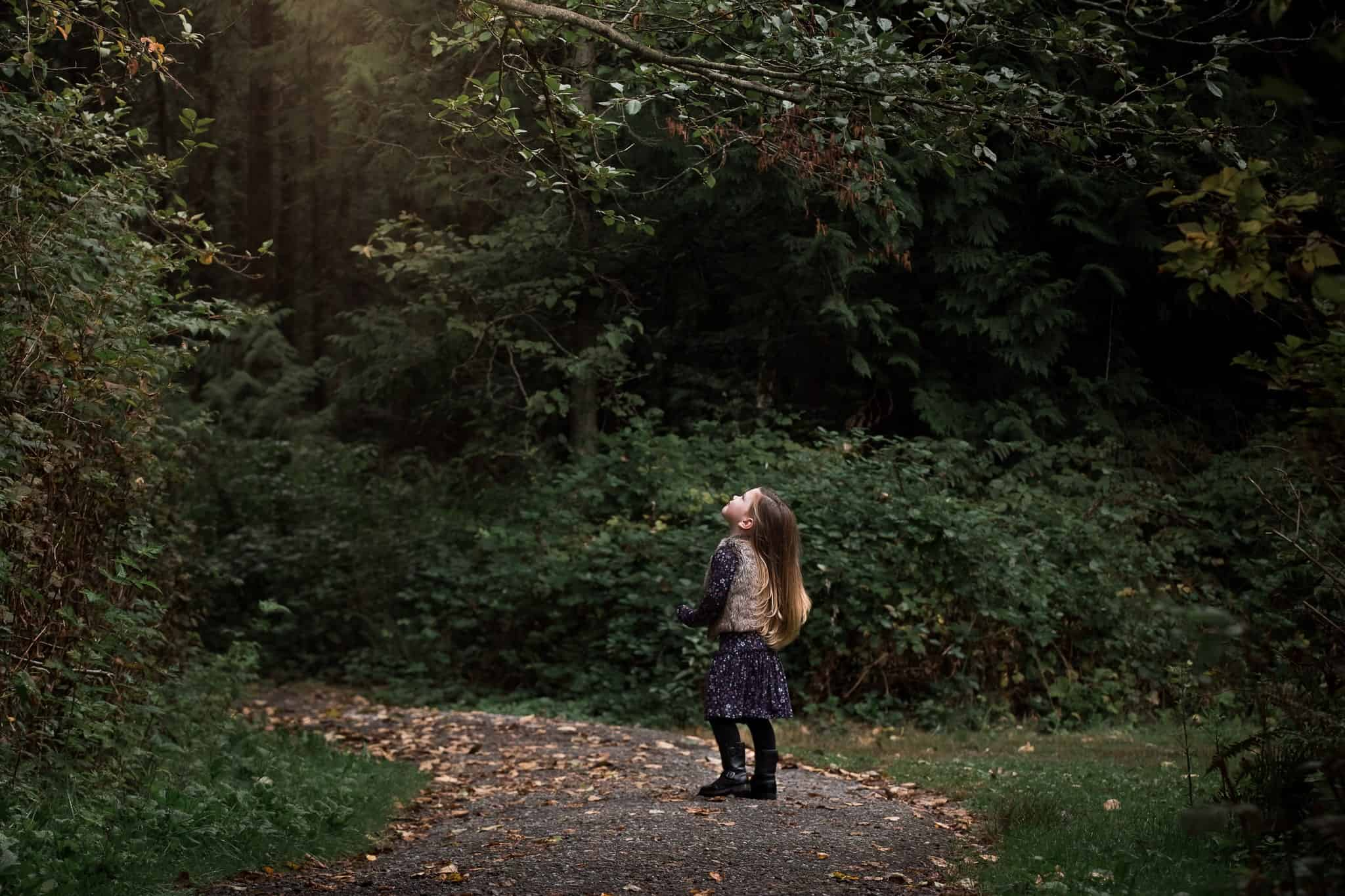 littler girl on a forest path looking up into the trees