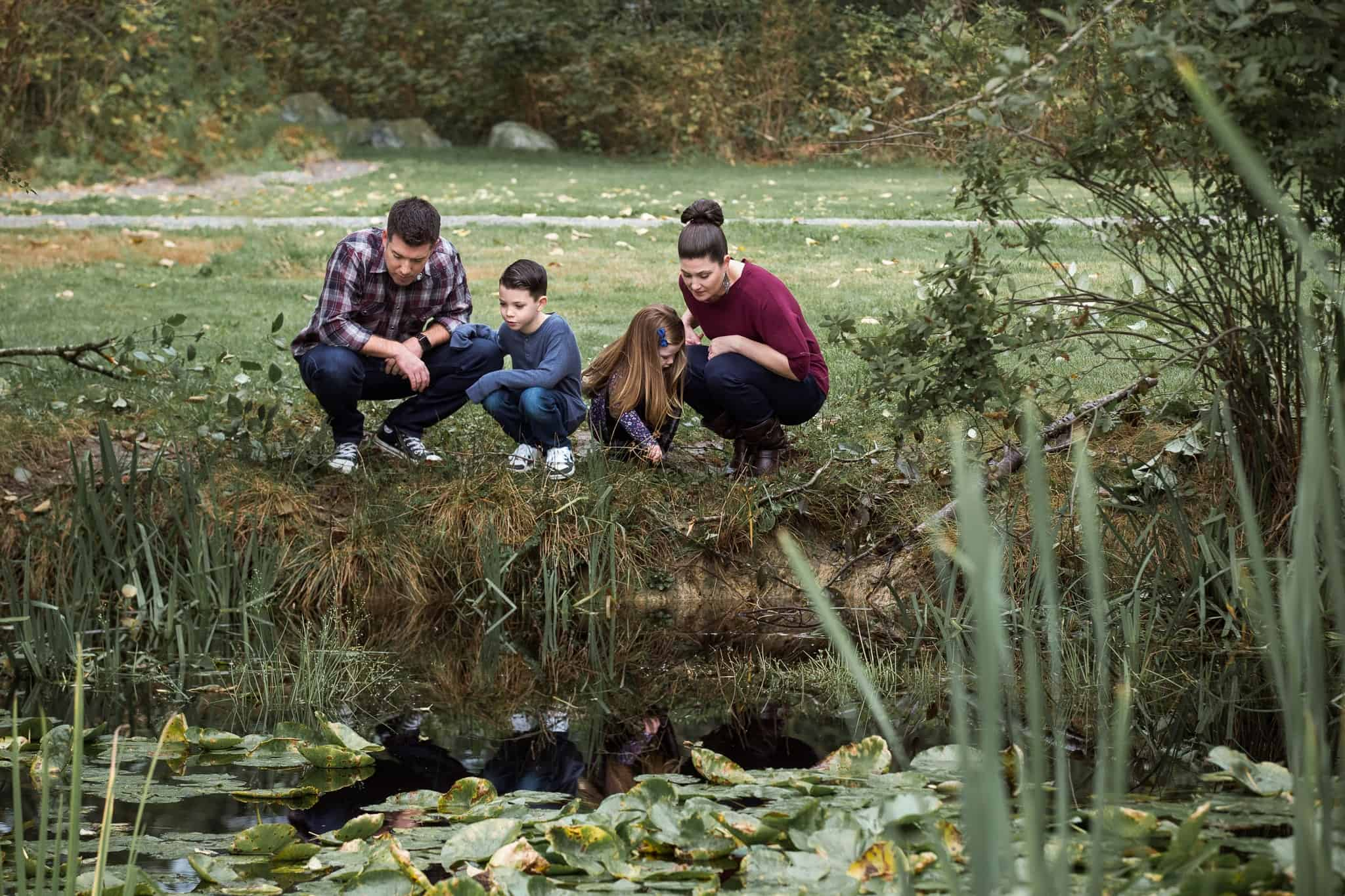 family of four kneeling by a pond looking into the water