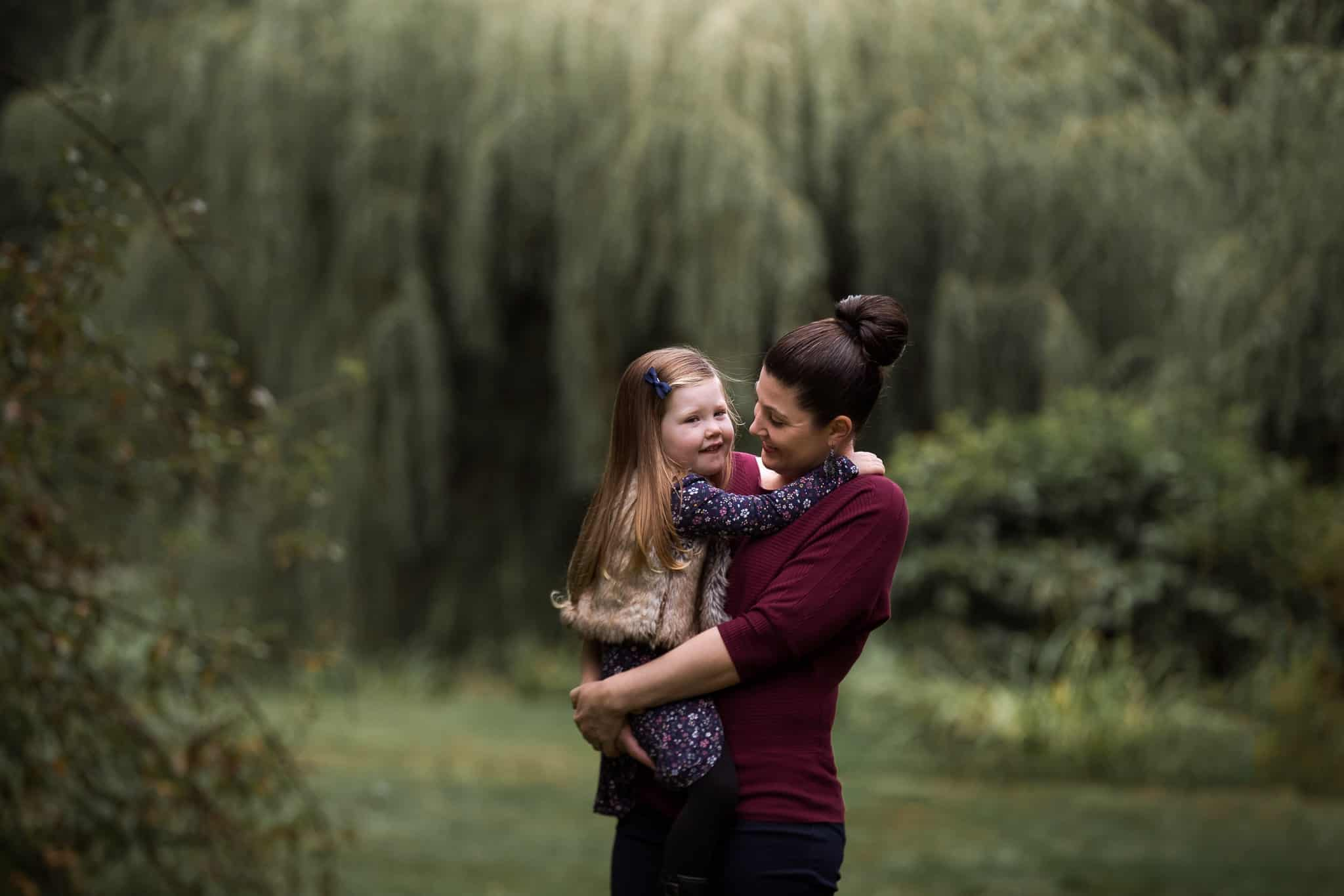 mom holding daughter and smiling
