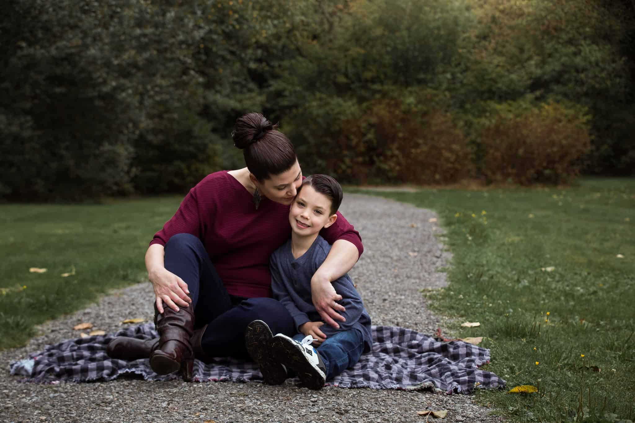 mom hugging her son close on a blanket