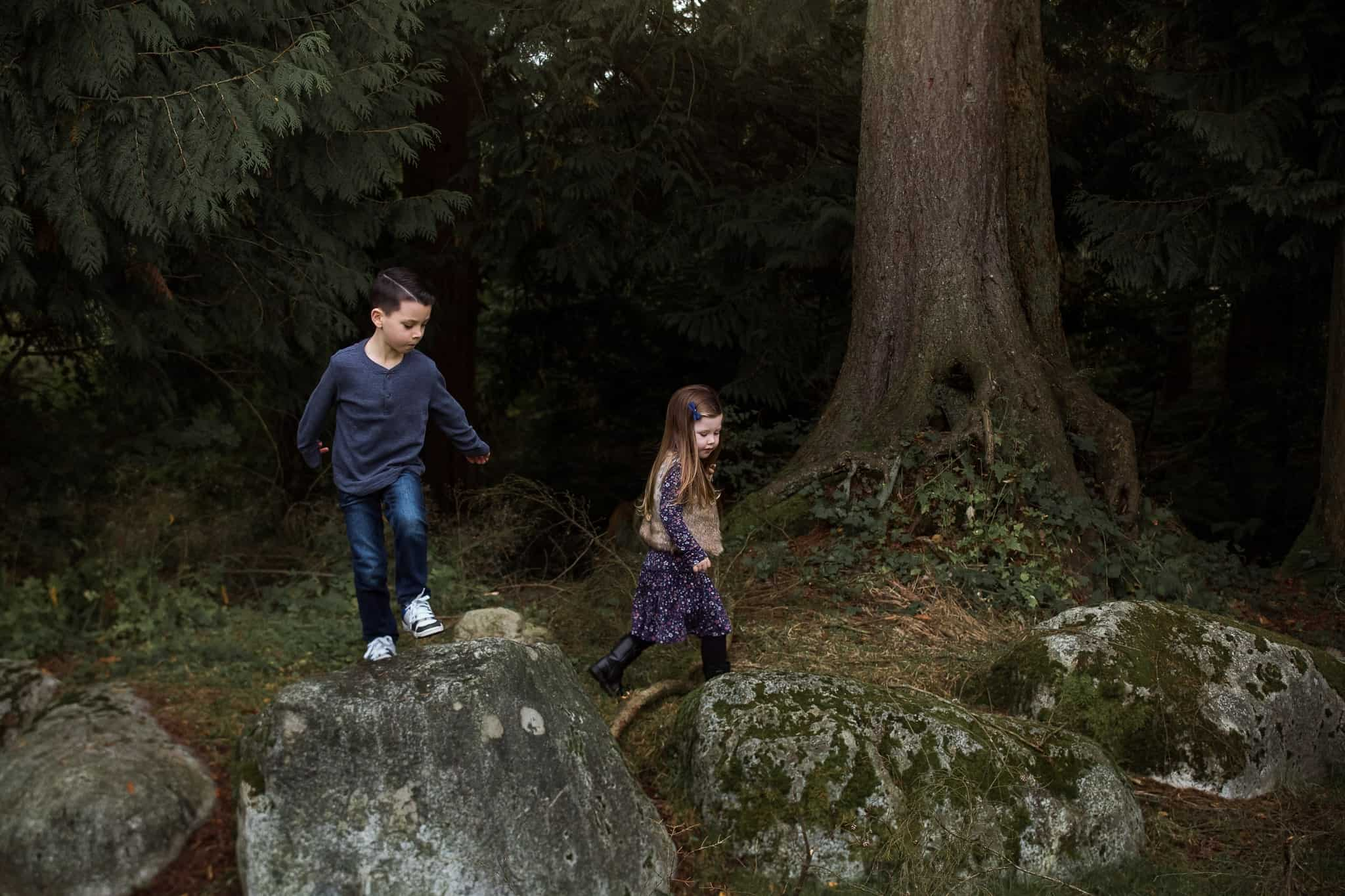 brother and sister hoping on rocks in a forest