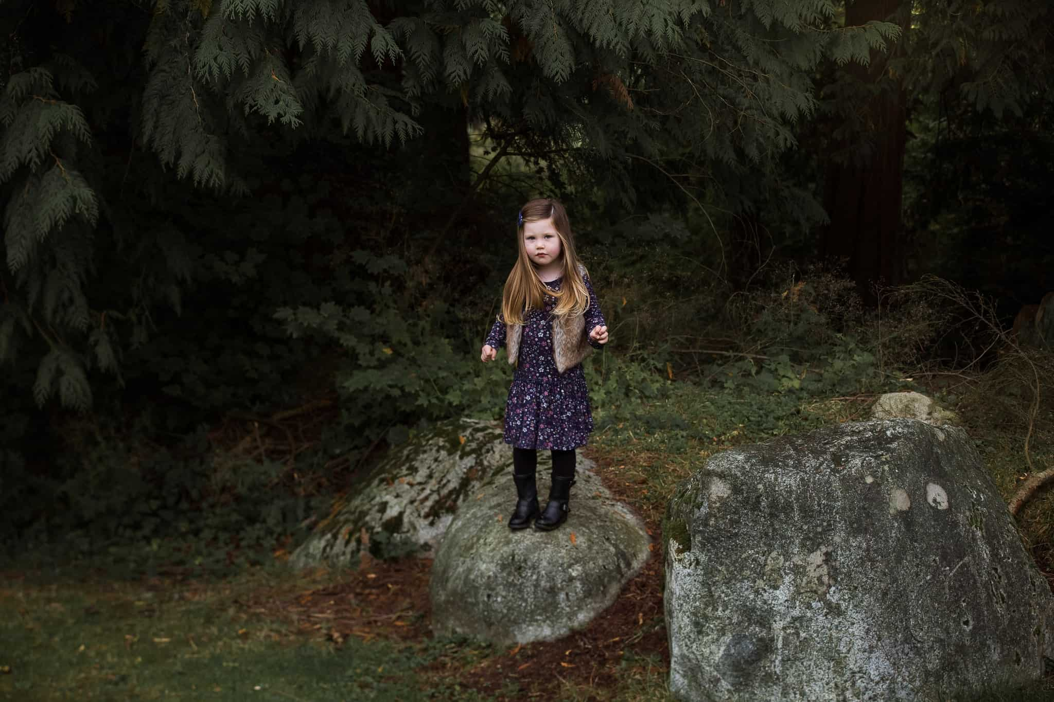 little girl standing on rocks in a forest