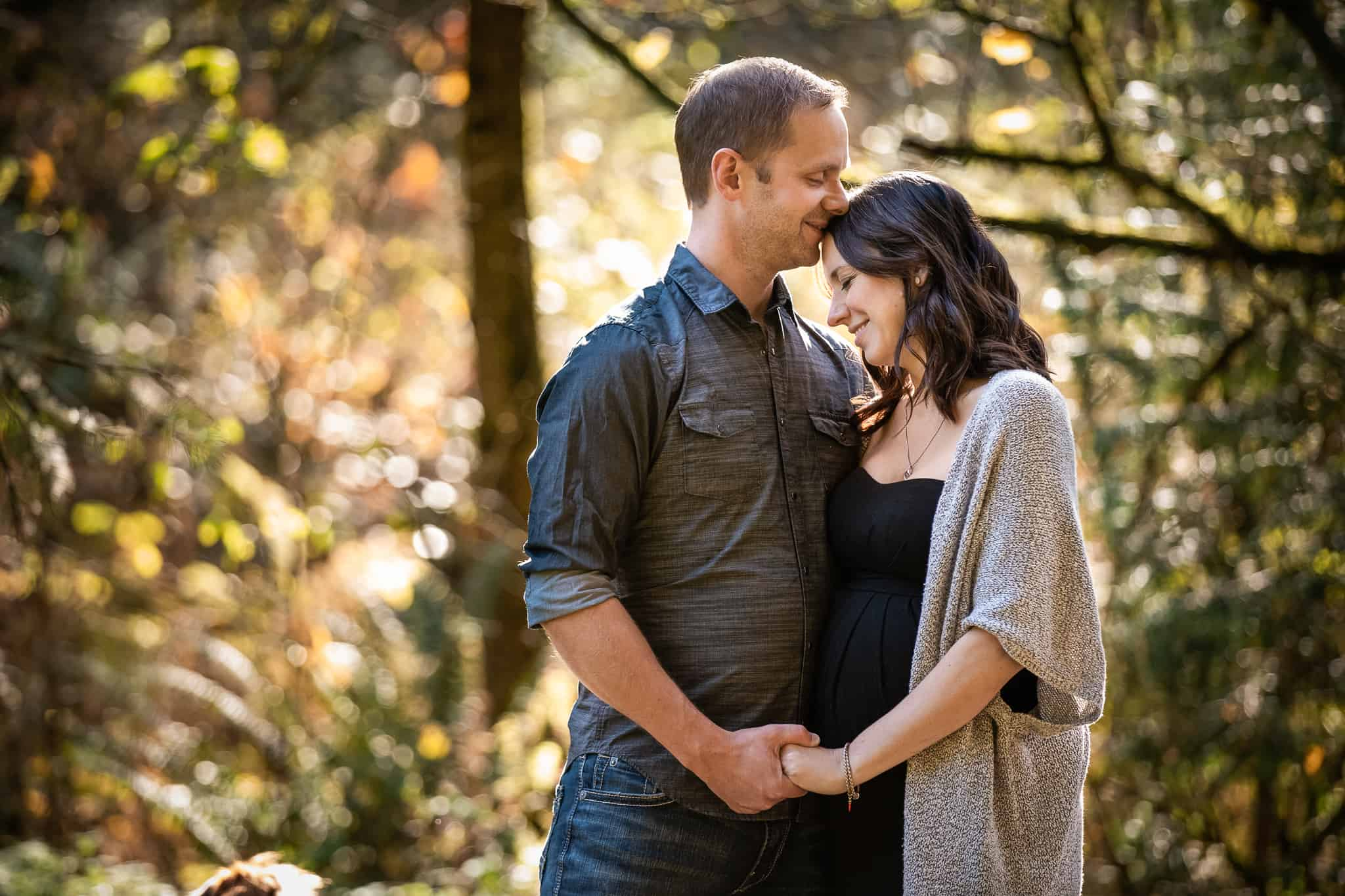 pregnant couple holding hands in fall light
