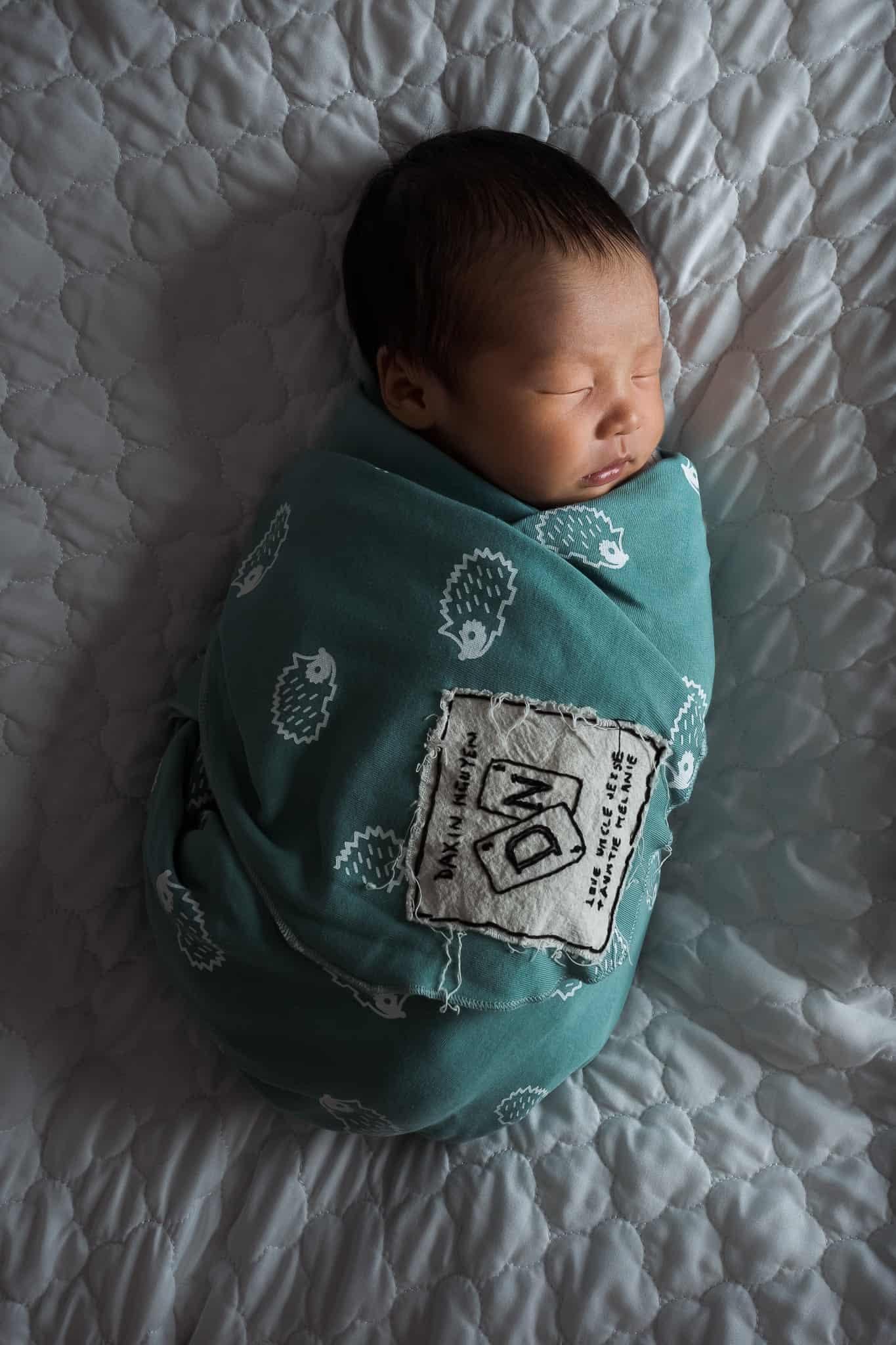 newborn baby swaddled turquoise wrap