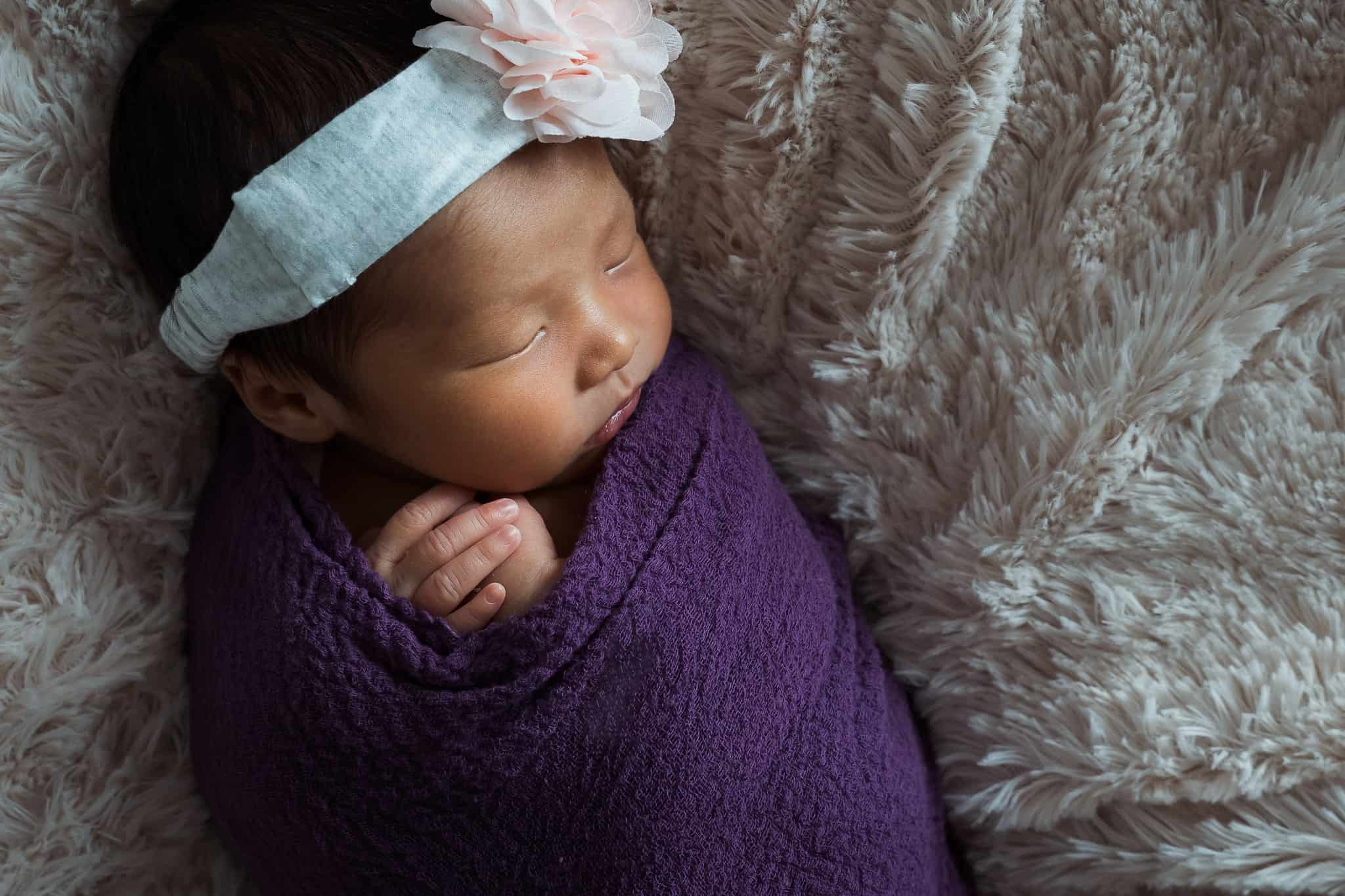 newborn baby swaddled with pink flower headband