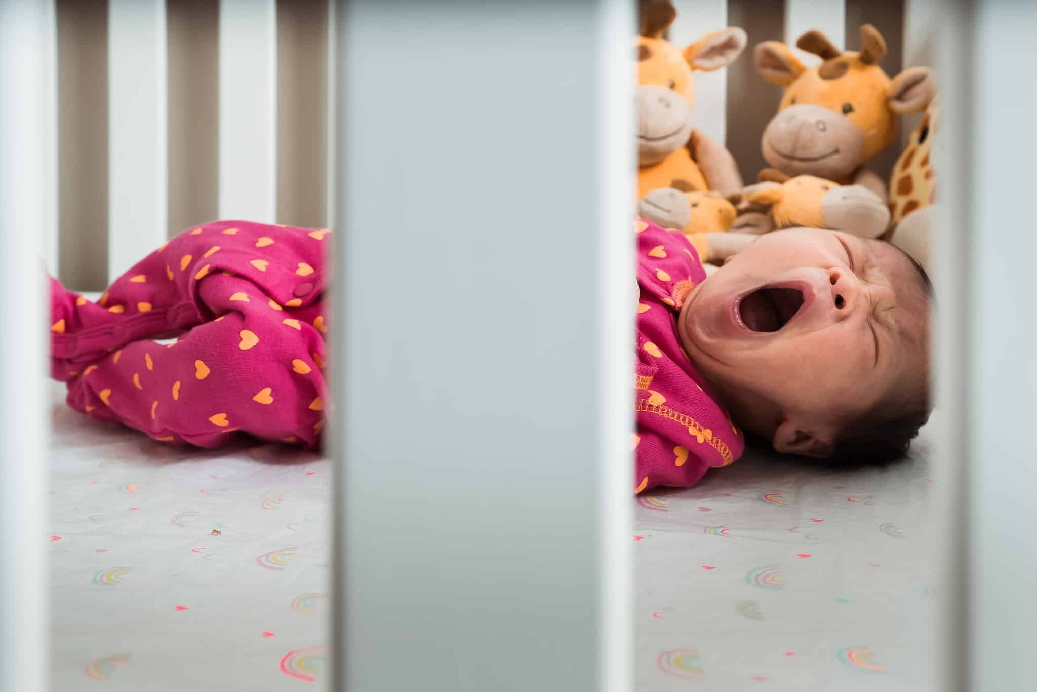 baby newborn yawning through crib bars with stuffed giraffes