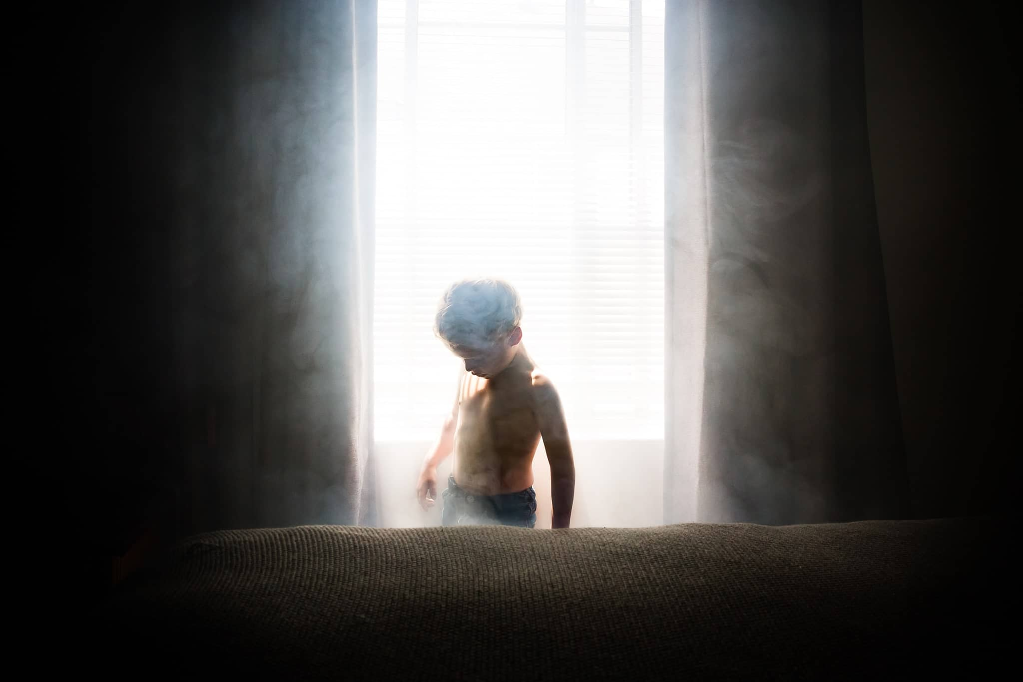 toddler boy emerging from smoke in sunlit window