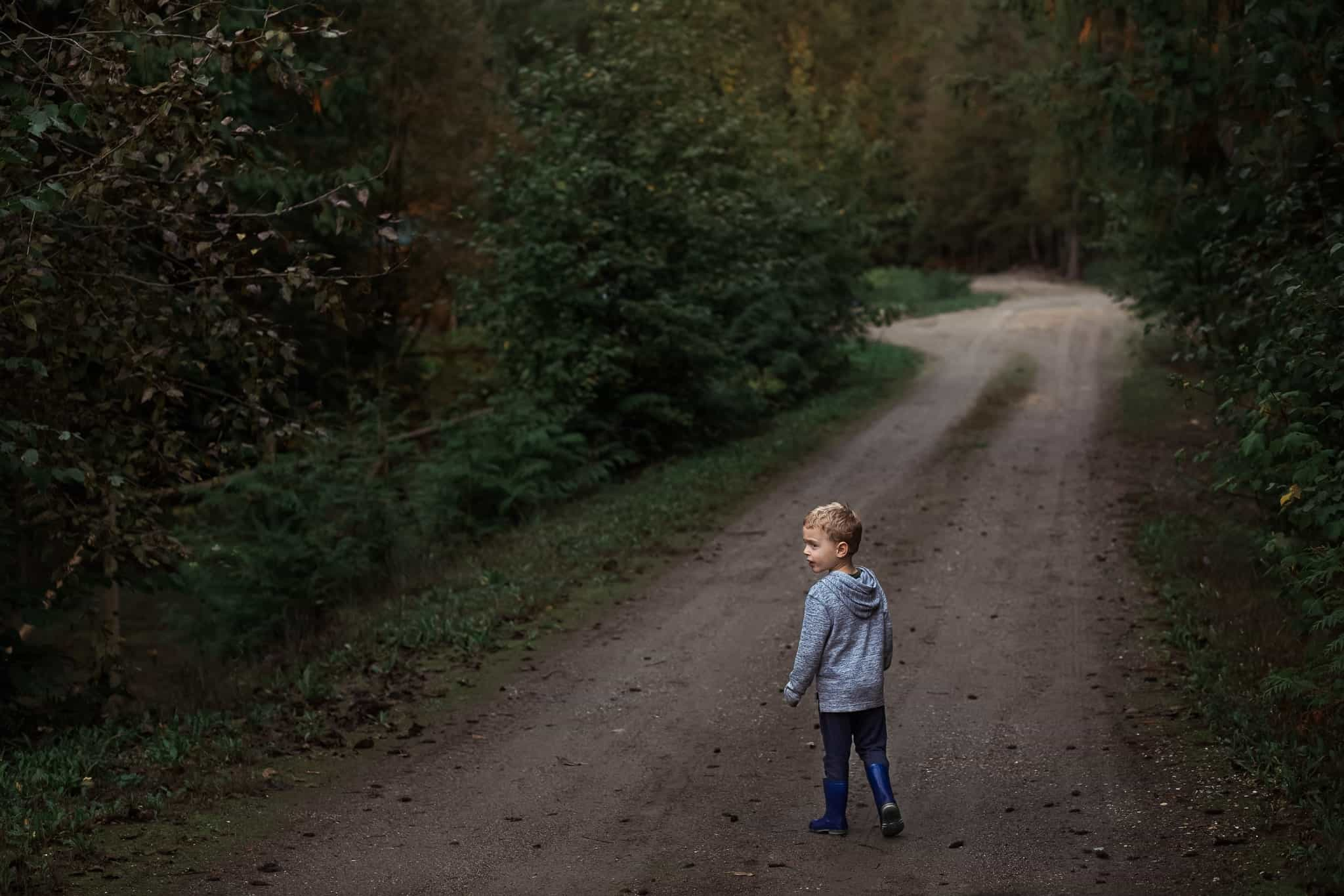 toddler boy walking forest path