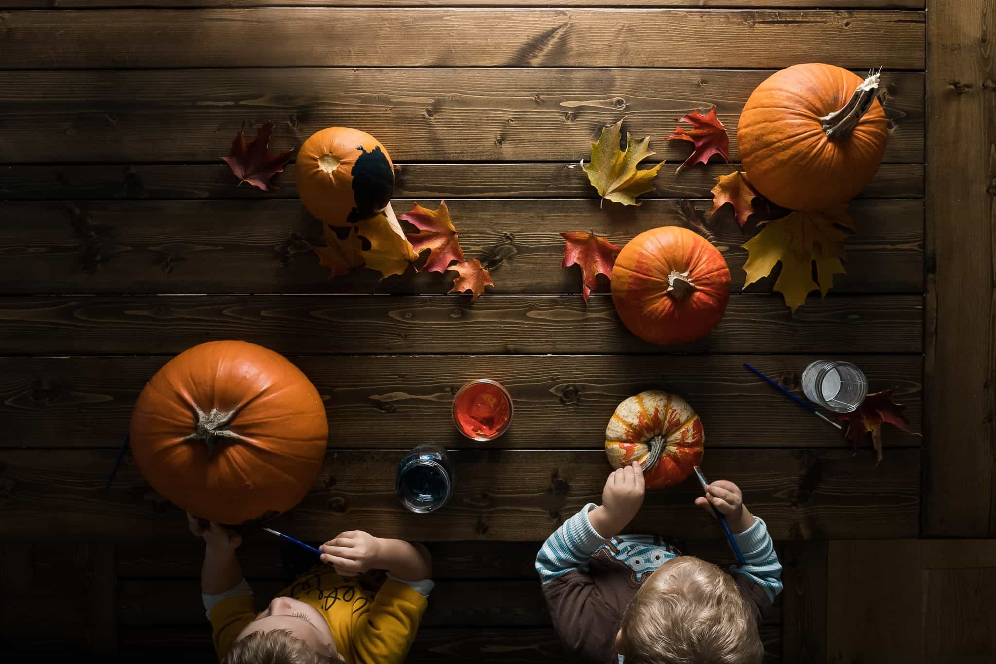 toddler boys painting pumpkins on wooden table