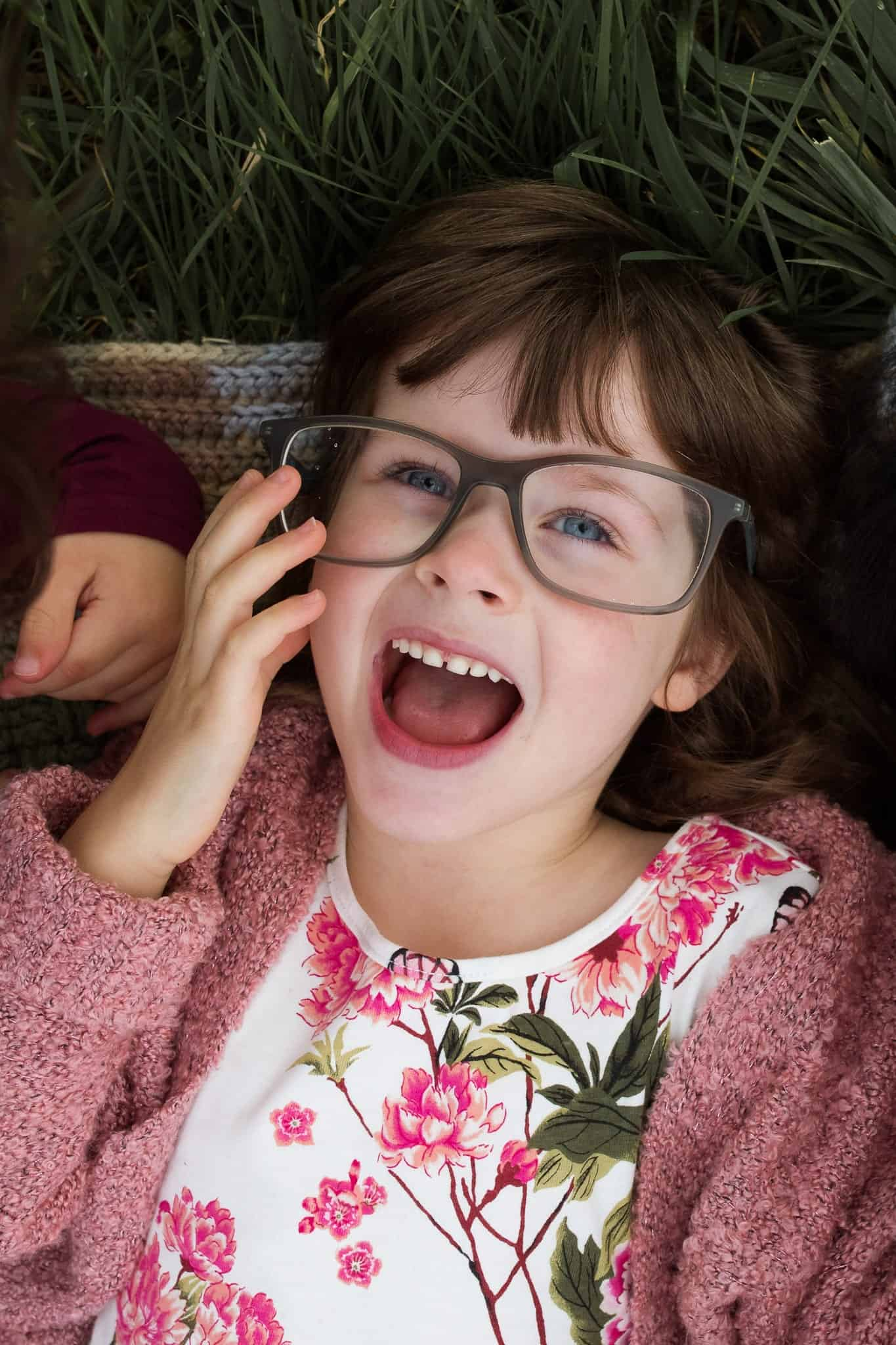 little girl laying on her back wearing her dad's glasses laughing