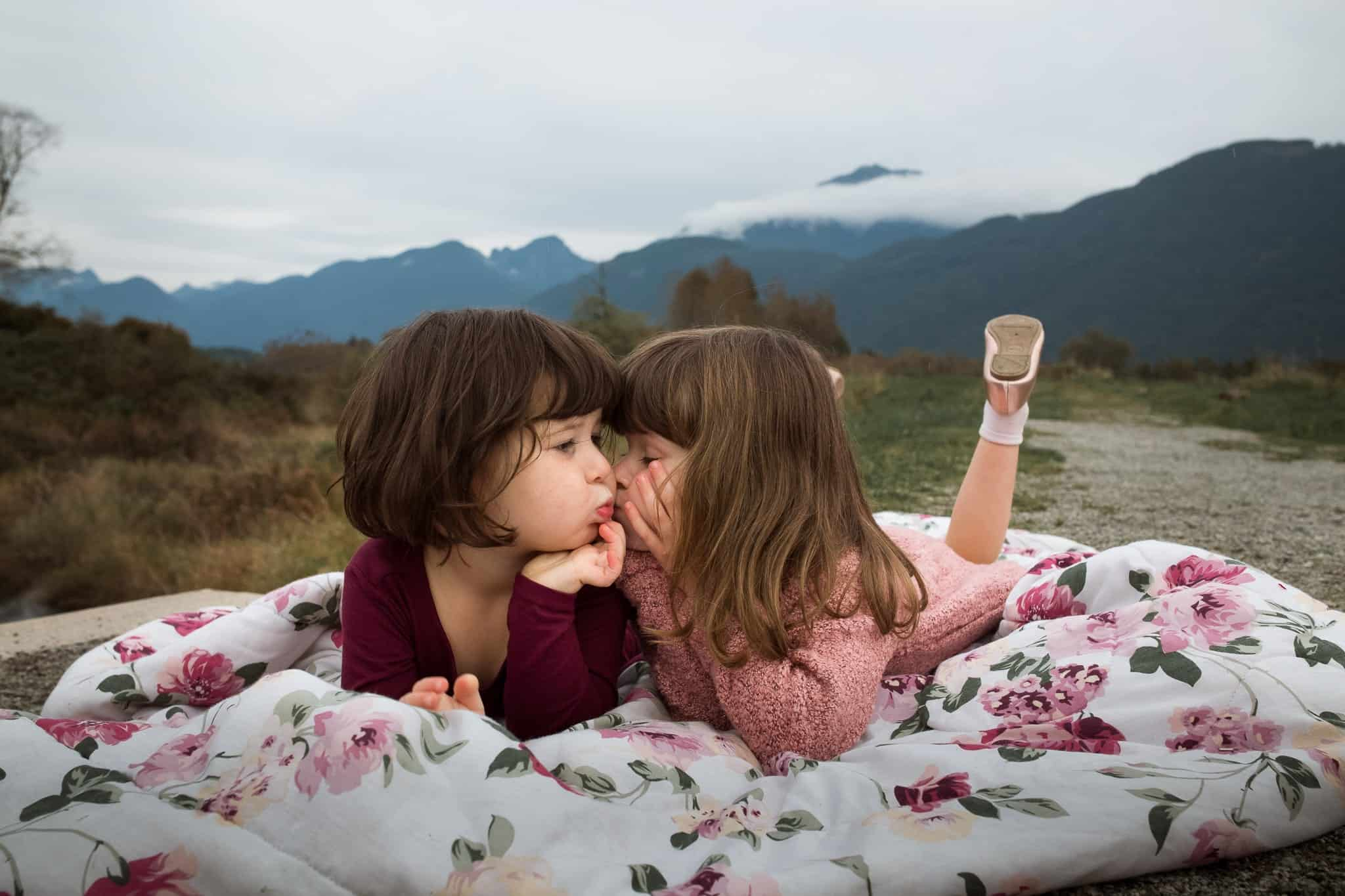 two girls laying on a blanket making kissy faces at each other
