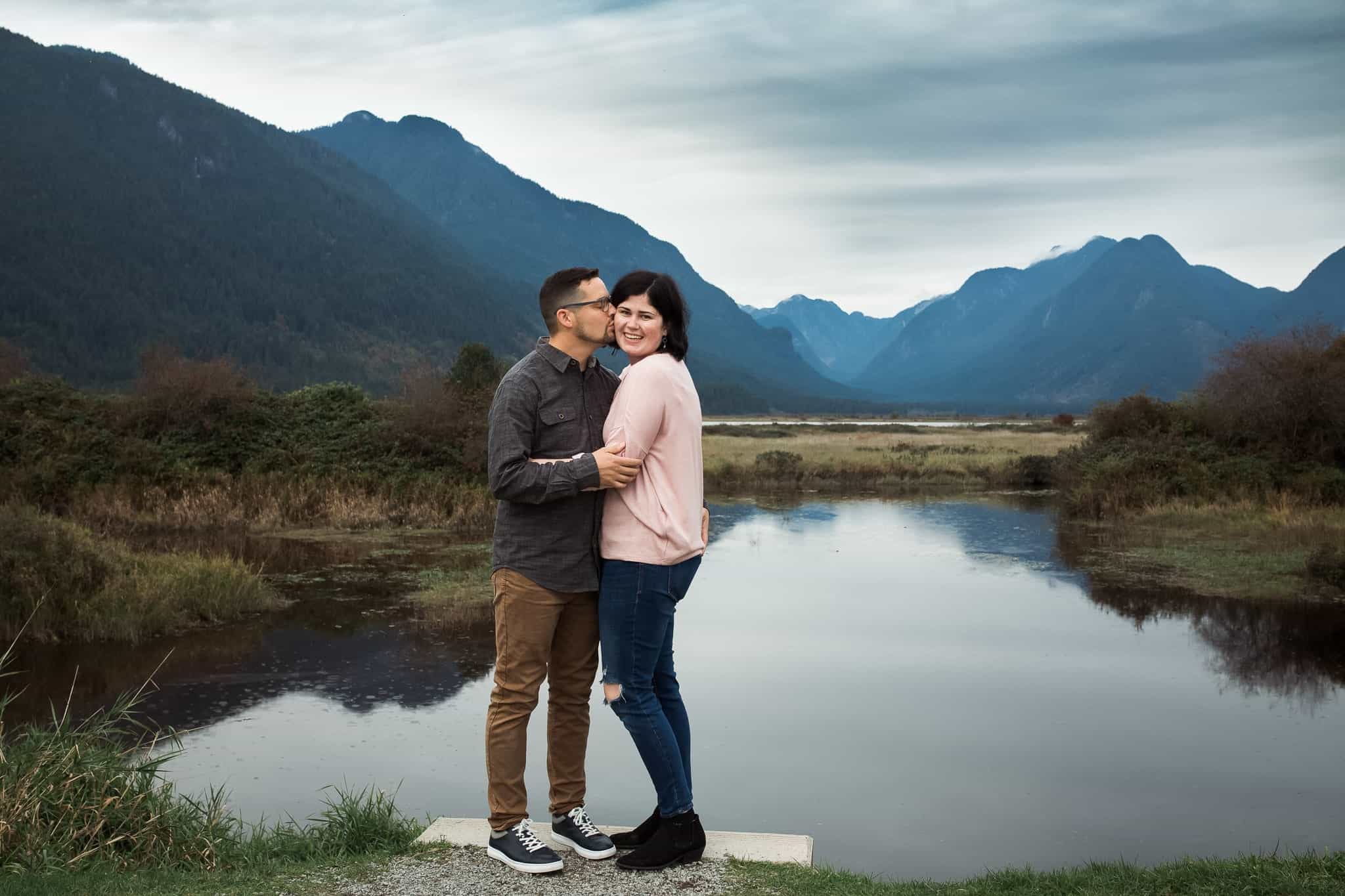 a couple standing on the edge of a lake with mountains in the background kissing