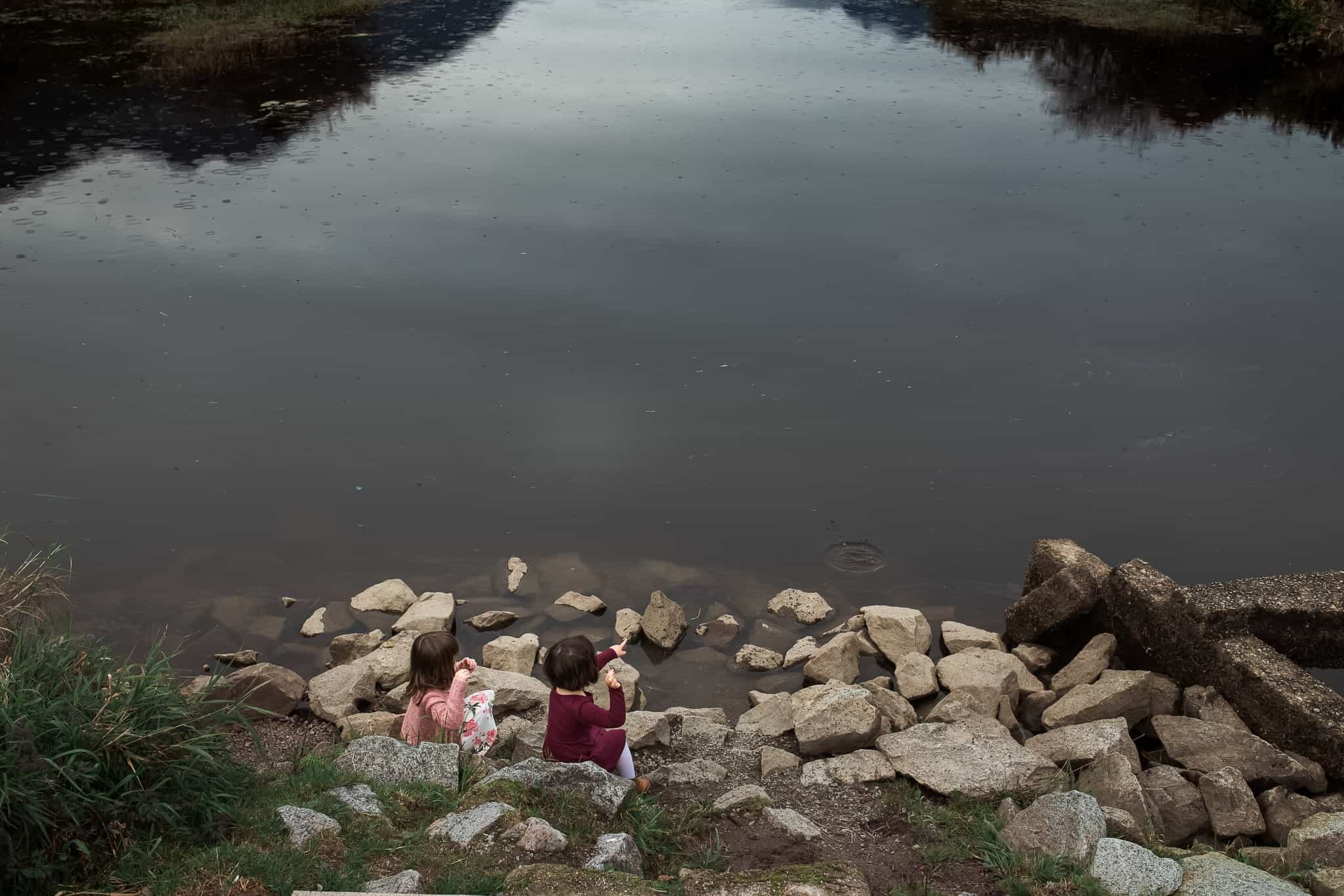 two girls throwing rocks into a still pond
