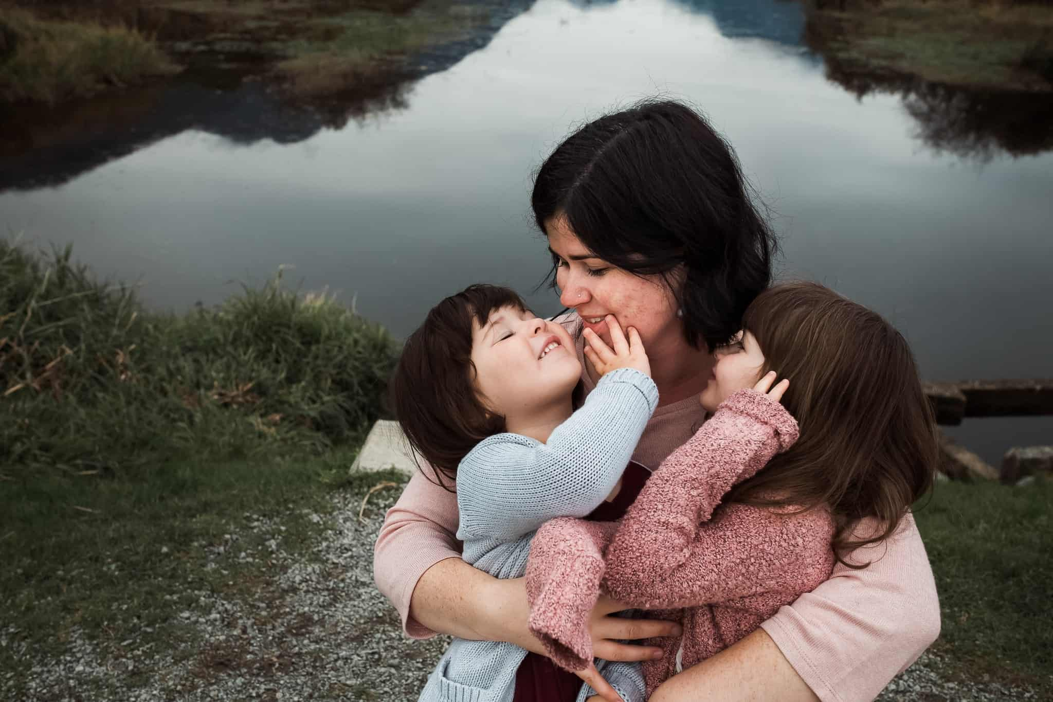 two little girls snuggling with their mom by a lake
