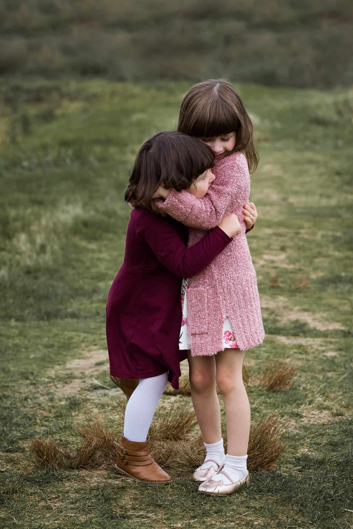 two toddler girls hugging