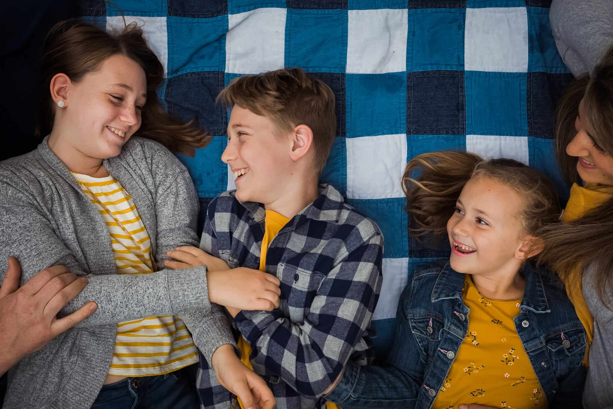 siblings laughing, laying on blanket with parents