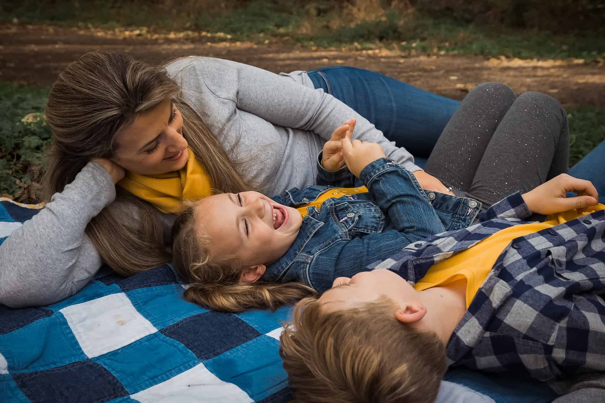 siblings laughing laying on blanket with mom