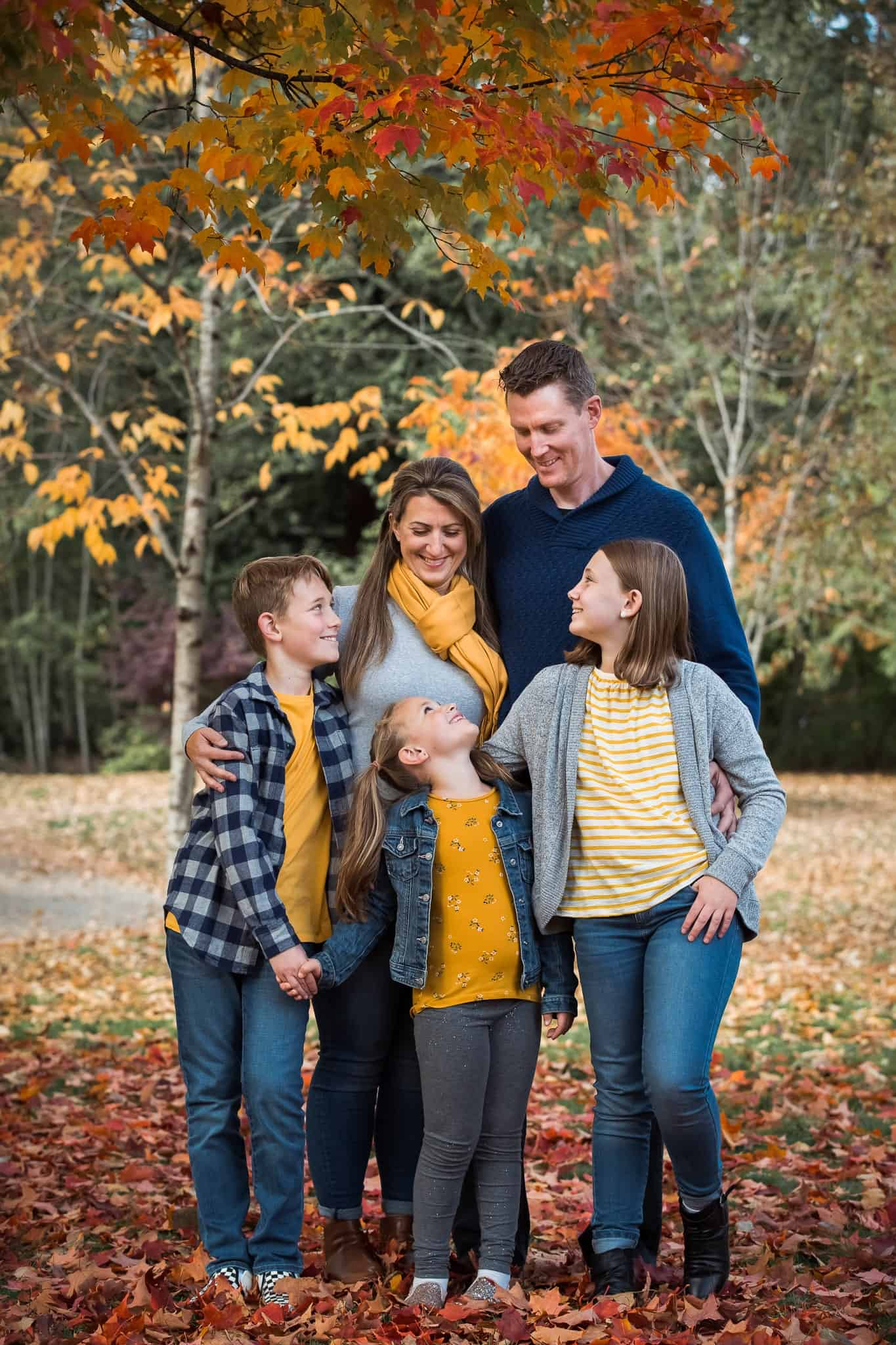 family of five standing for a photo under autumn trees