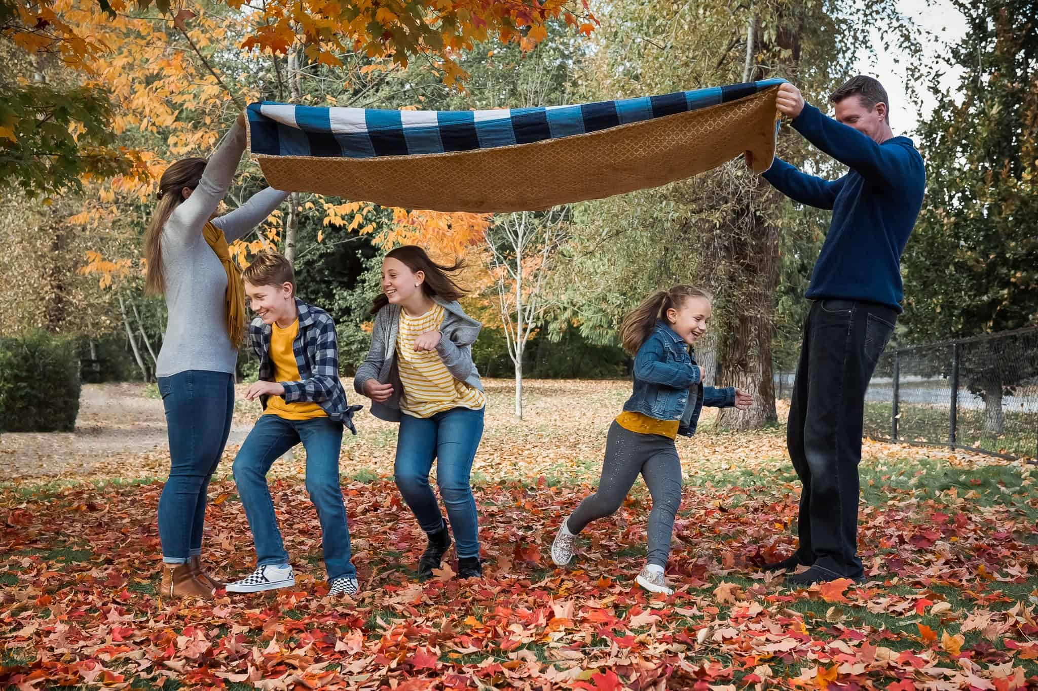 family running and playing in autumn leaves