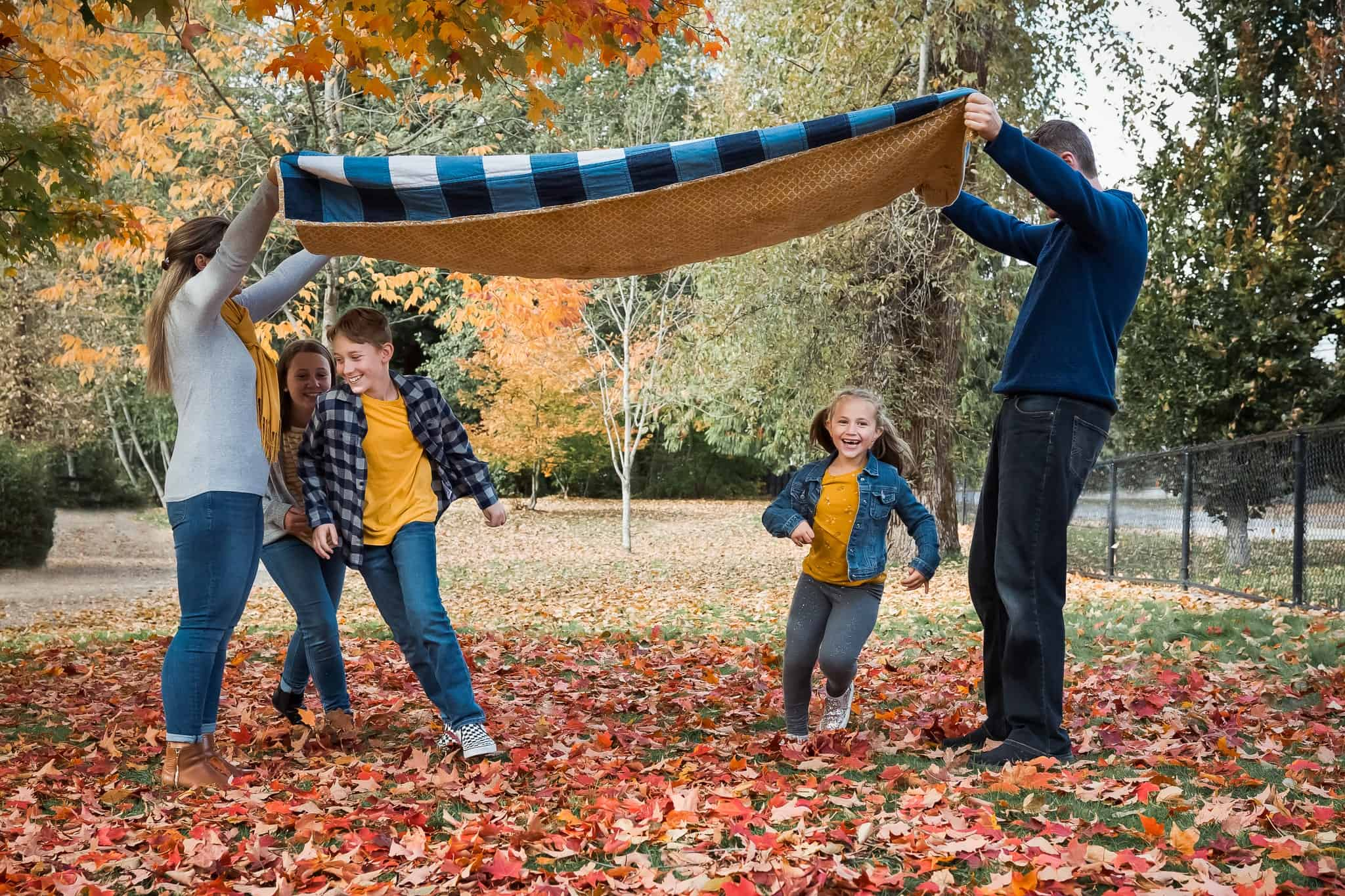 family running under a blanket in autumn leaves