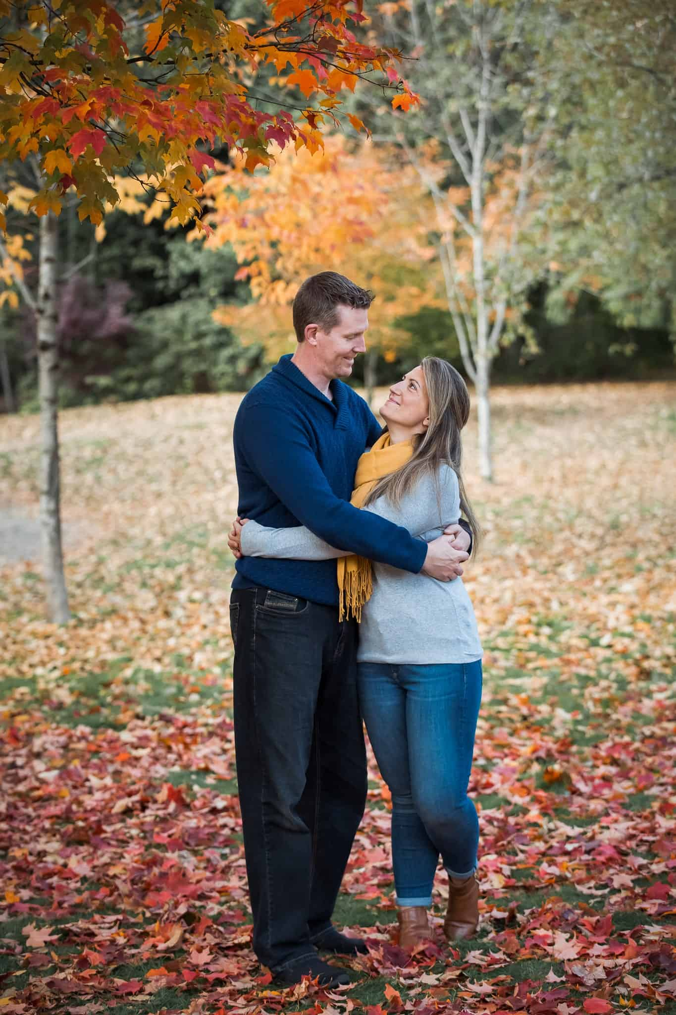 couple holding each other under autumn trees
