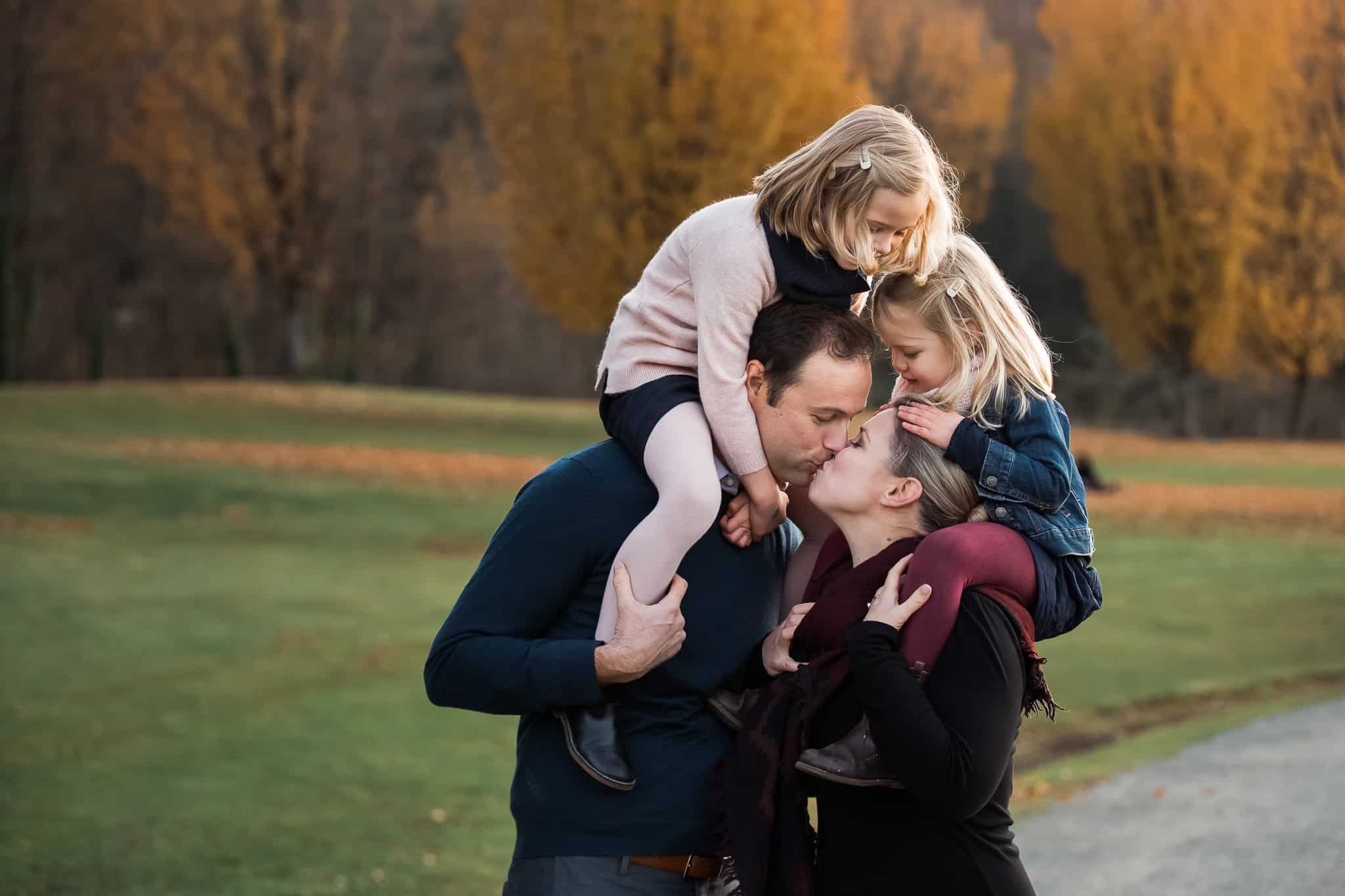 mom and dad kissing with daughters on their shoulders